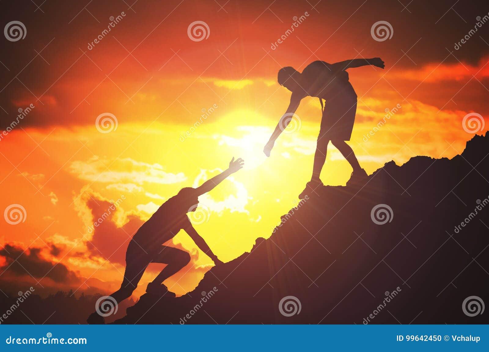 Το άτομο δίνει το χέρι βοηθείας Σκιαγραφίες των ανθρώπων που αναρριχούνται στο βουνό στο ηλιοβασίλεμα