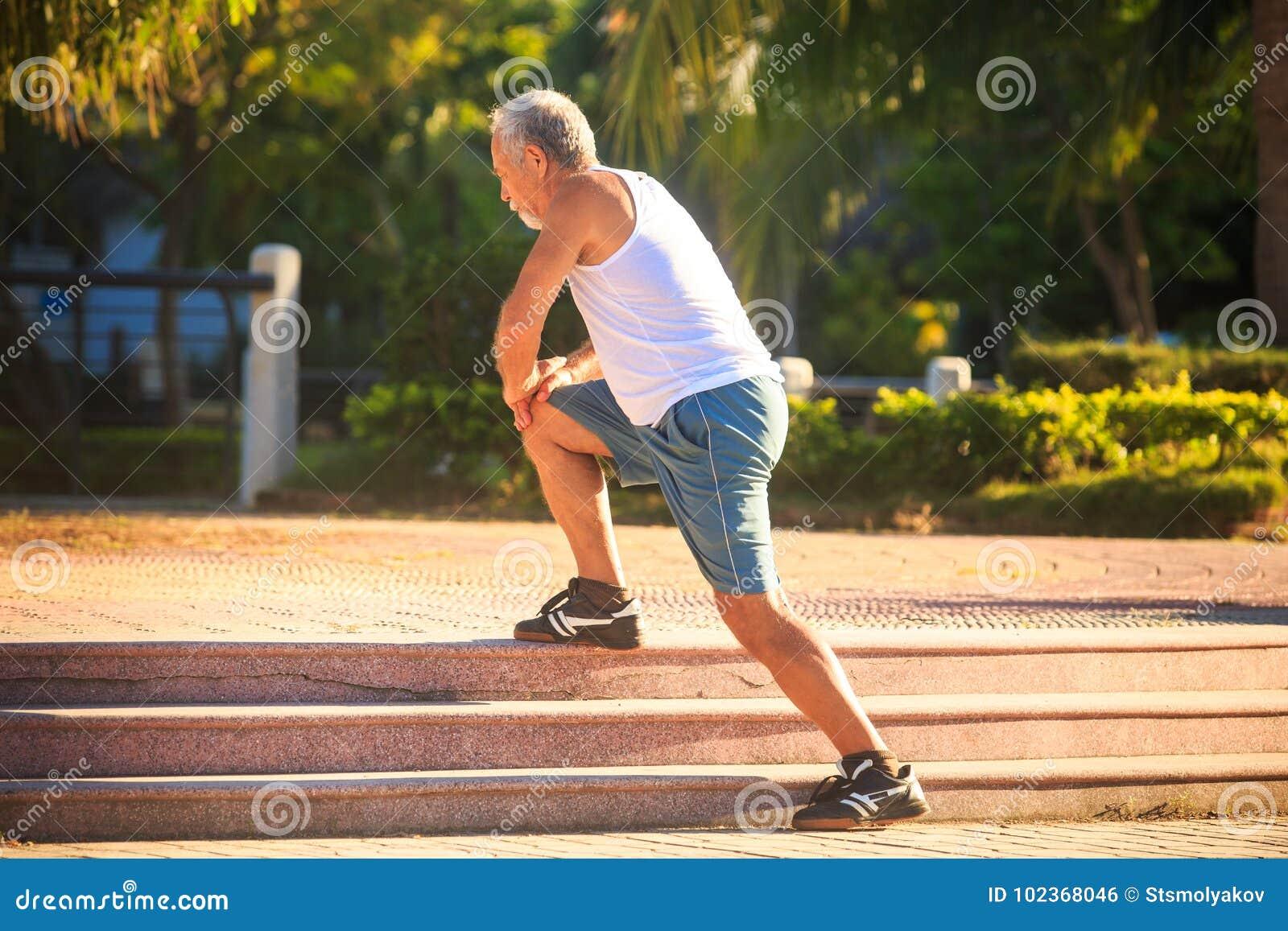 Το άτομο κάνει τις στάσεις οκλαδόν ασκήσεων πρωινού στο γόνατο στα πέτρινα βήματα