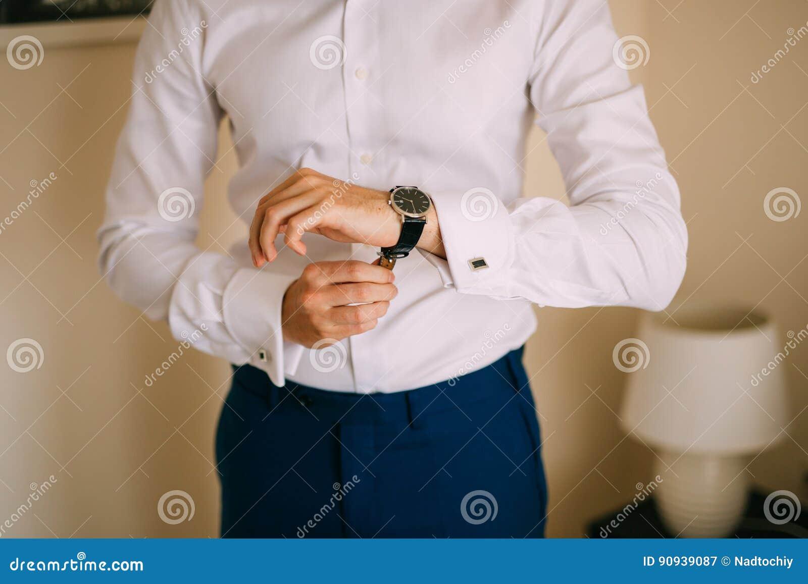 49a54e7efc03 Το άτομο κουμπώνει το μανικετόκουμπο στο γαλλικό άσπρο πουκάμισο  πολυτέλειας μανικιών μανσετών