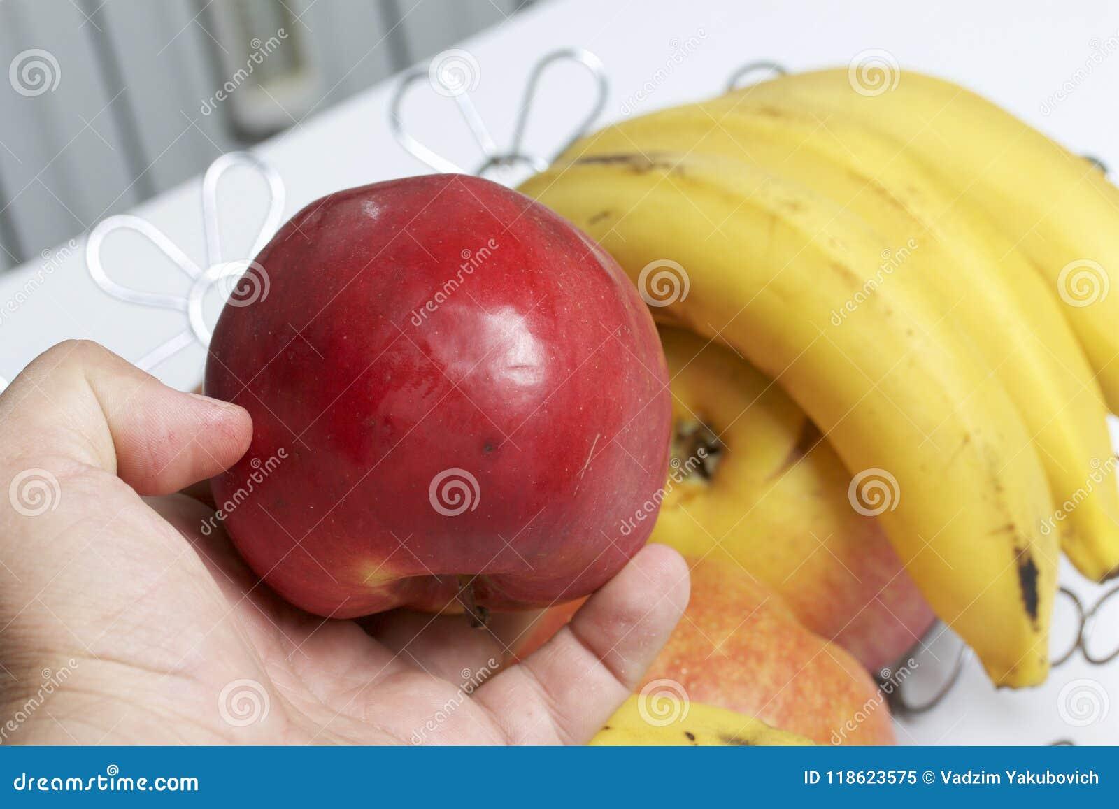 Το άτομο κρατά ένα κόκκινο μήλο στο χέρι του Υπάρχει ένα καλάθι φρούτων στο υπόβαθρο Διάφορες μήλα και μπανάνες