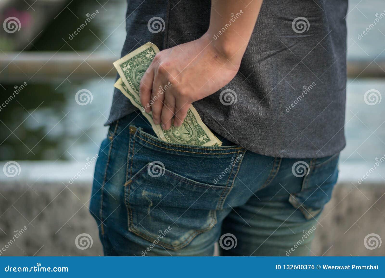 Το άτομο κρατά τα χρήματα αμερικανικών δολαρίων στην τσέπη τζιν