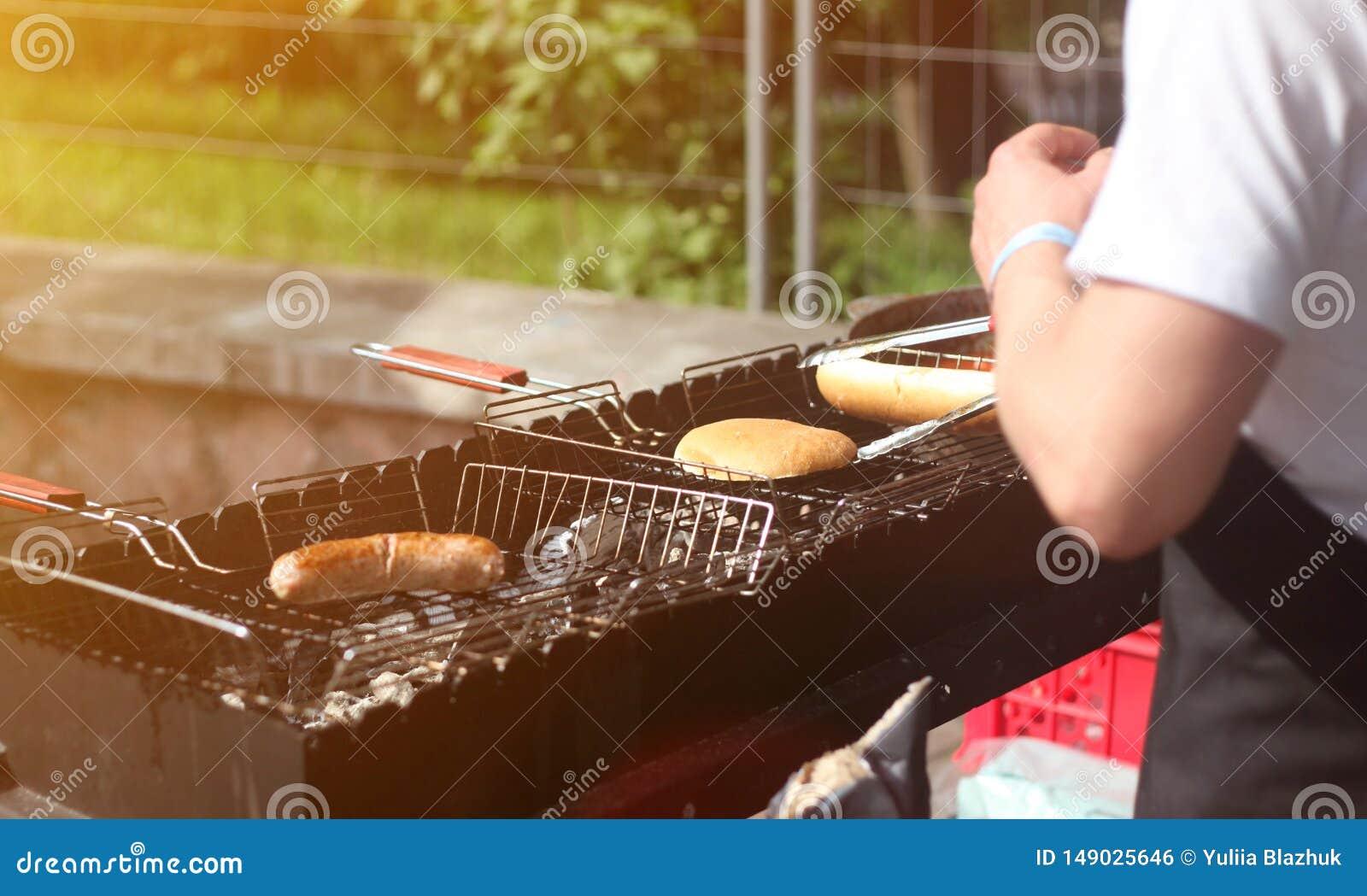 Το άτομο μαγειρεύει τα λουκάνικα και τα κουλούρια για τα χοτ-ντογκ και τα burgers στη σχάρα υπαίθρια
