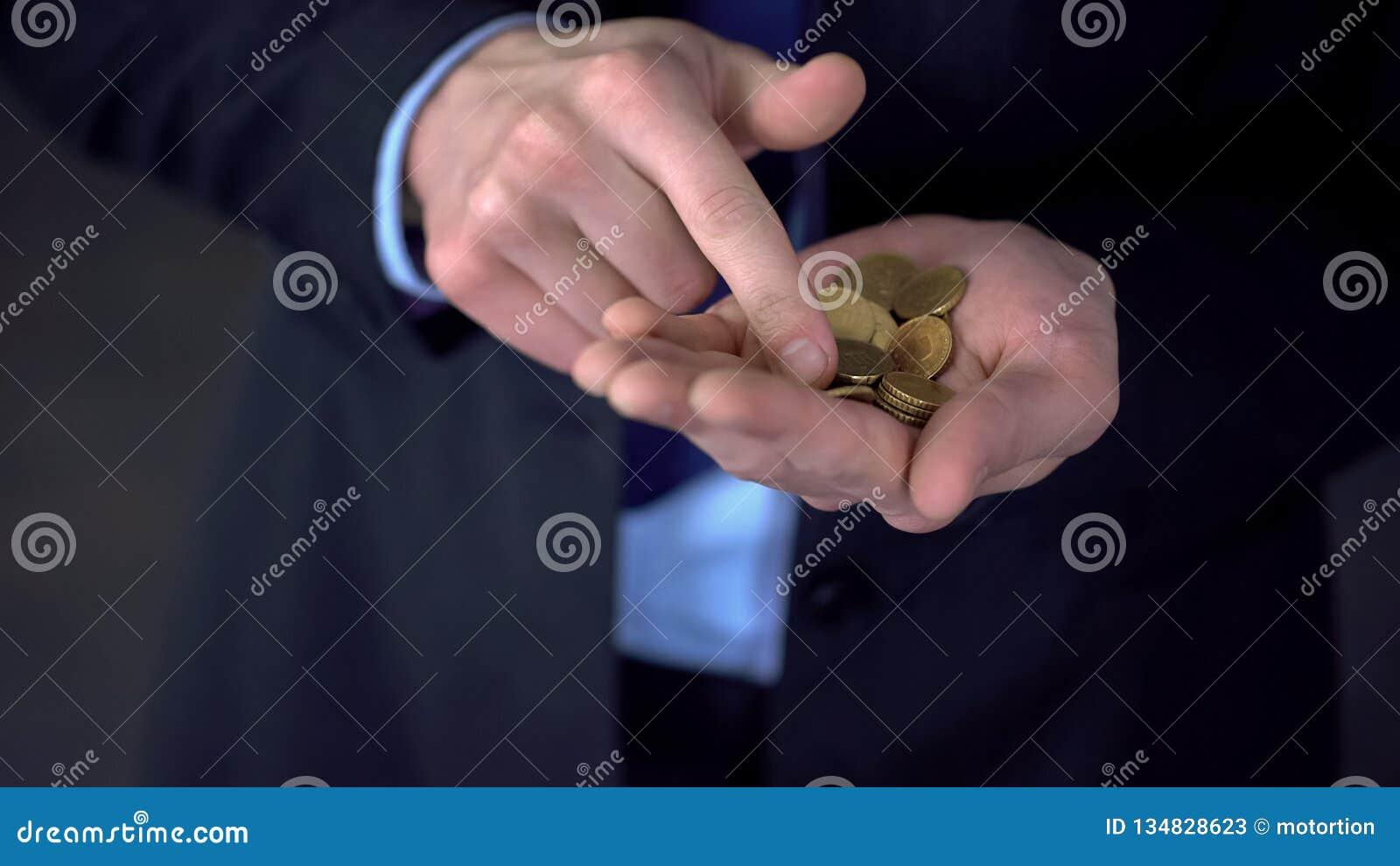 Το άτομο με τα μεσαίου εισοδήματος μετρώντας νομίσματα, χαμηλός μισθός, δαπάνες υπερβαίνει τα εισοδήματα