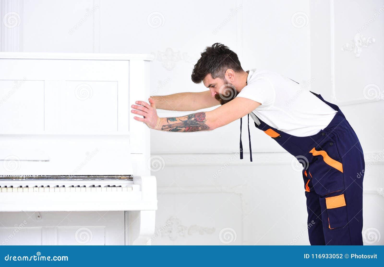 Το άτομο με τη γενειάδα και mustache, εργαζόμενος στις φόρμες ωθεί το πιάνο, το άσπρο υπόβαθρο Έννοια υπηρεσιών παράδοσης Κινήσει