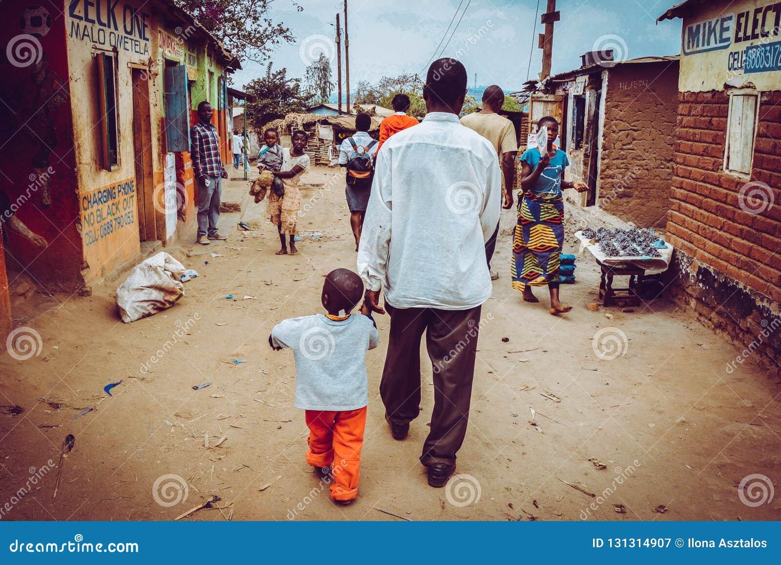 Το άτομο περπατά με το παιδί του στην οδό στην Αφρική