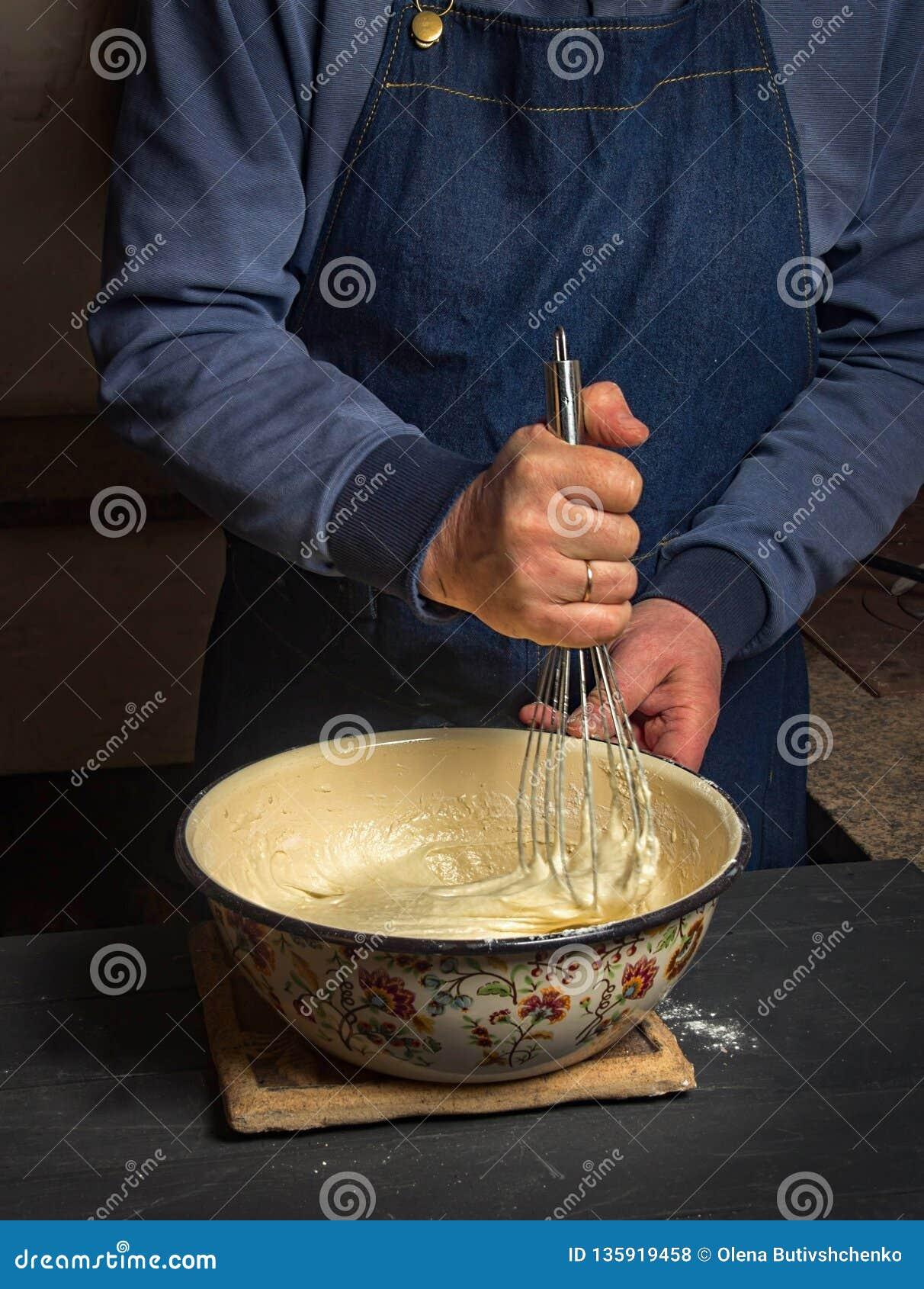Το άτομο που κρατά χτυπά ελαφρά για το κτύπημα της ζύμης Κάνετε τη ζύμη για τις τηγανίτες