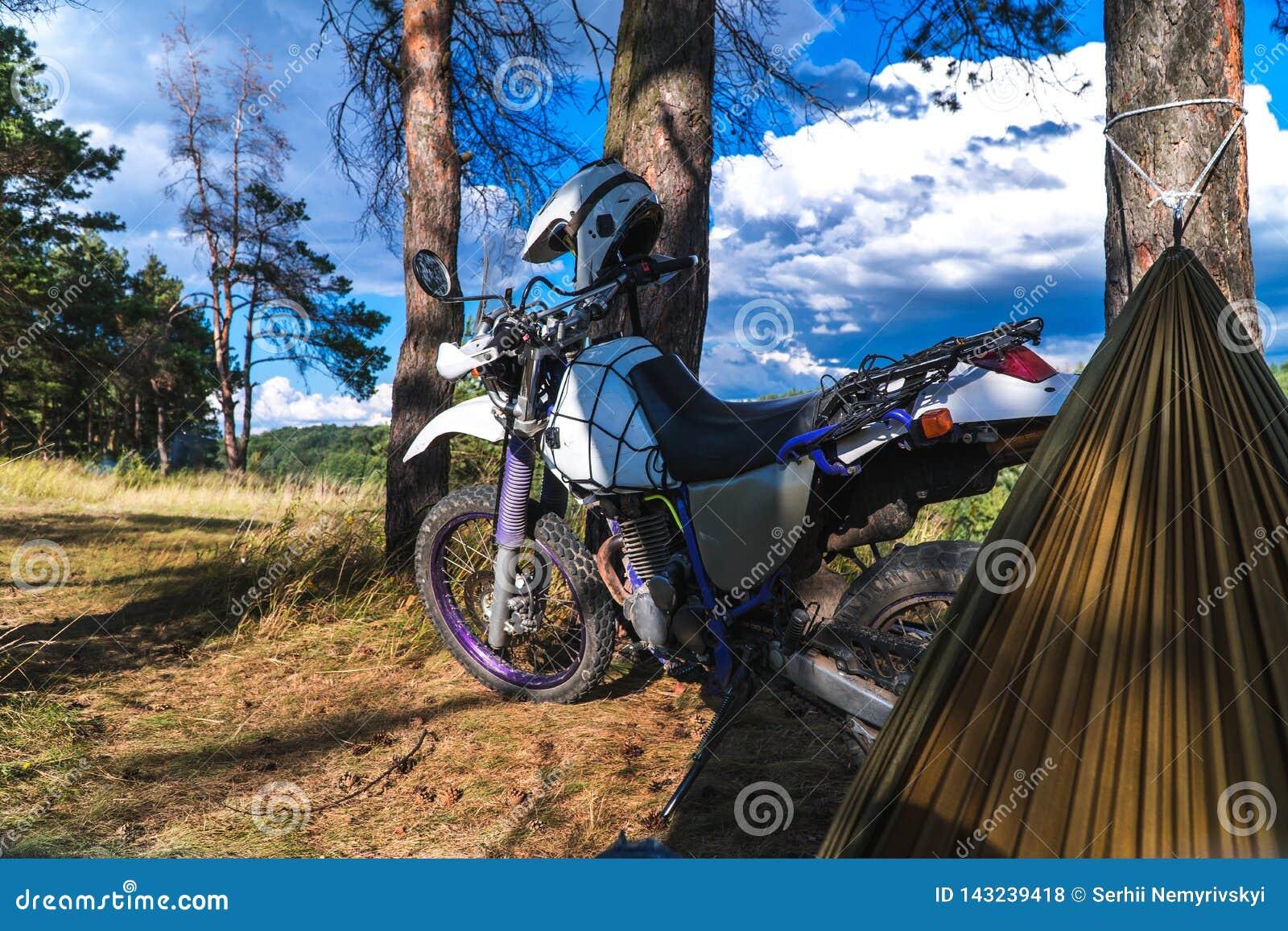 Το άτομο σε μια αιώρα στο δασικό βουνό πεύκων, υπαίθριος ταξιδιώτης χαλαρώνει, enduro από την οδική μοτοσικλέτα
