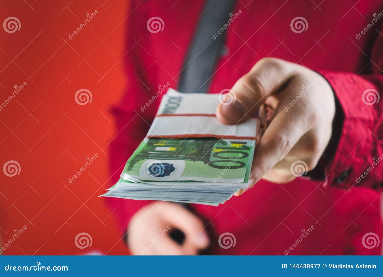το άτομο στο κόκκινο κοστούμι άντεξε ένα wad των χρημάτων στο χέρι του στο κόκκινο υπόβαθρο