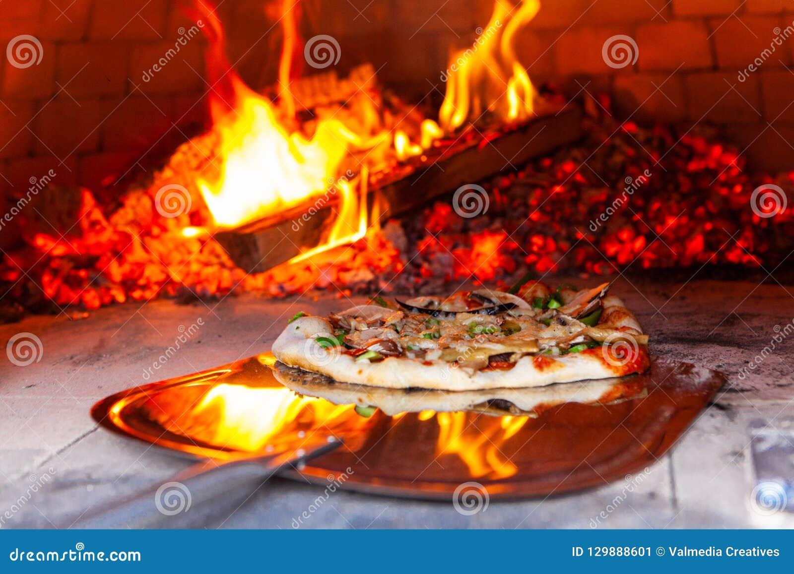 Το άτομο τοποθετεί μια πρόσφατα έτοιμη πίτσα σε έναν υπαίθριο φούρνο ψωμιού -