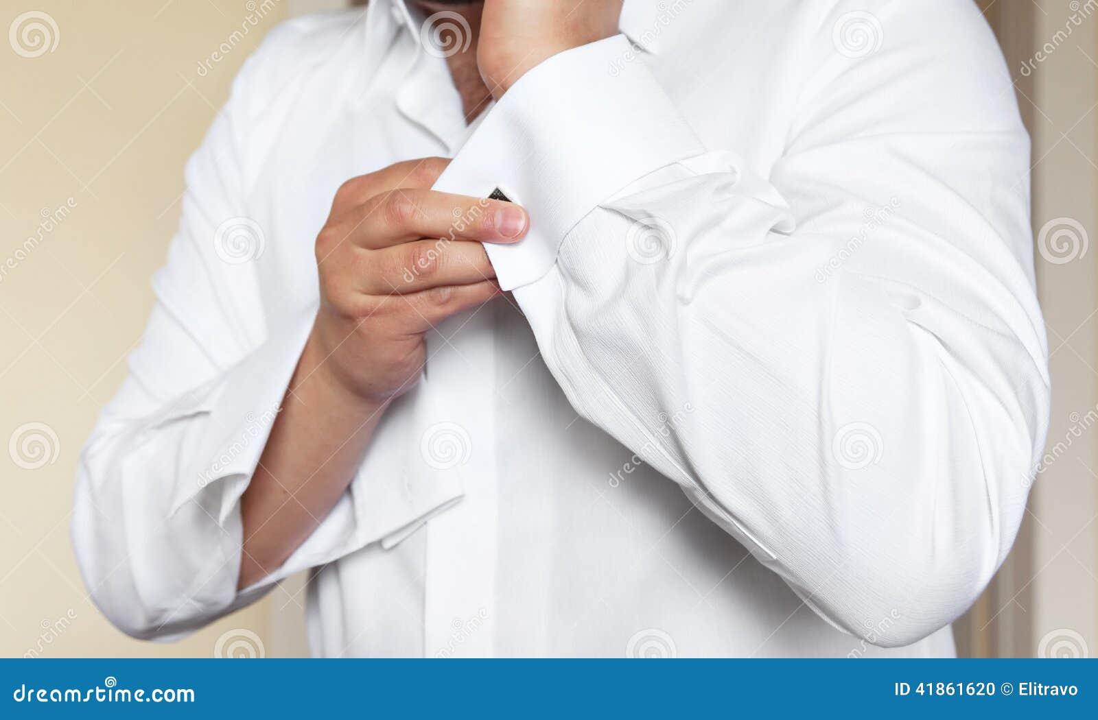 23a10cf0d3b2 Το άτομο βάζει τα μανικετόκουμπα στα άσπρα πουκάμισα μανικιών Στοκ ...