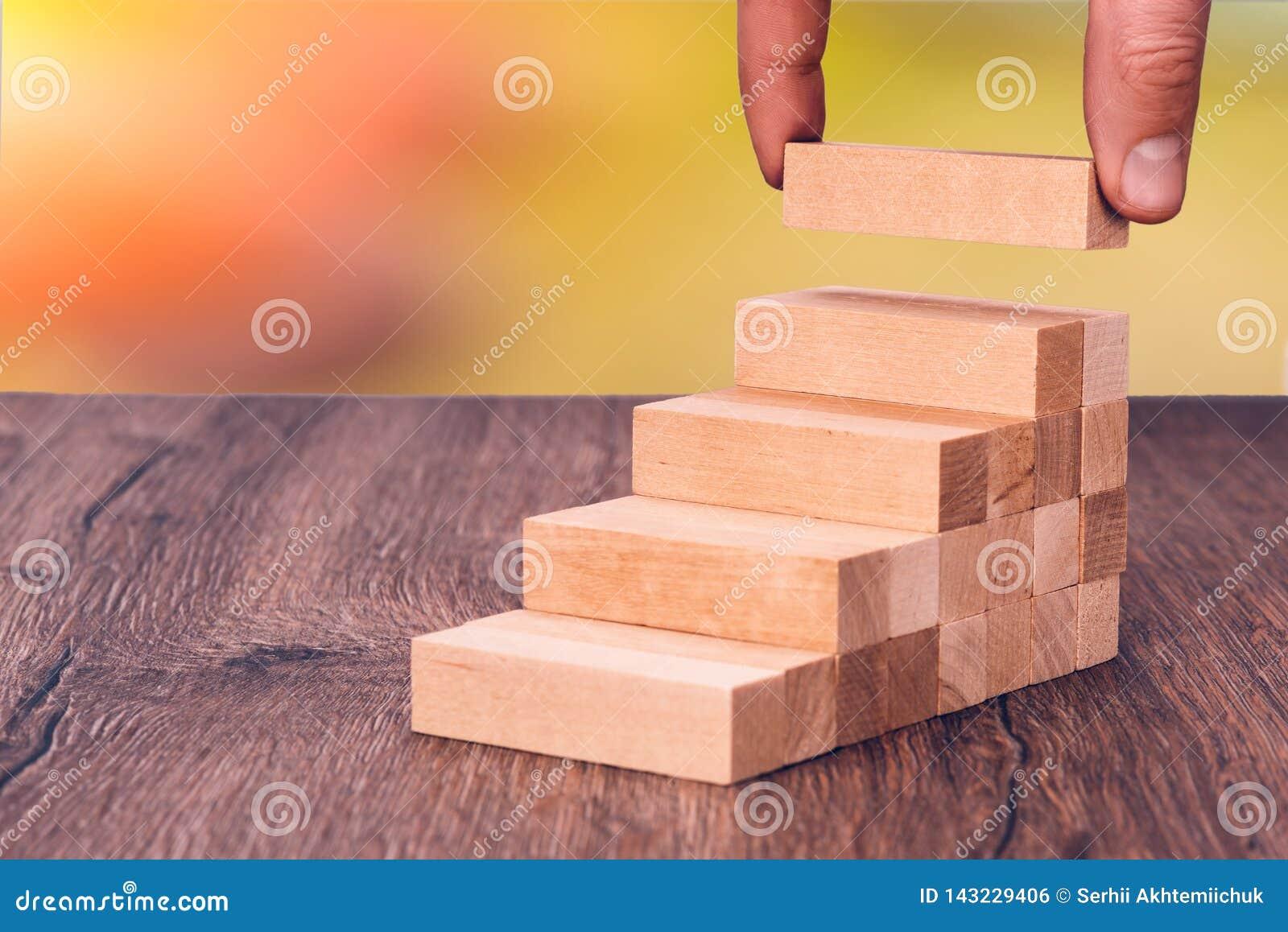 Το άτομο χτίζει μια ξύλινη σκάλα Έννοια: σταθερή ανάπτυξη