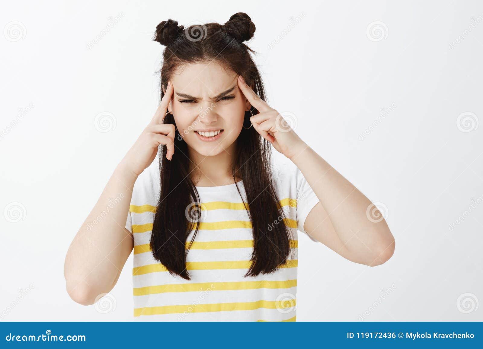 Το έντονο πιεσμένο χαριτωμένο κορίτσι στην καθιερώνουσα τη μόδα κίτρινη μπλούζα, που, κρατώντας τα δάχτυλα στους ναούς, προσπάθει
