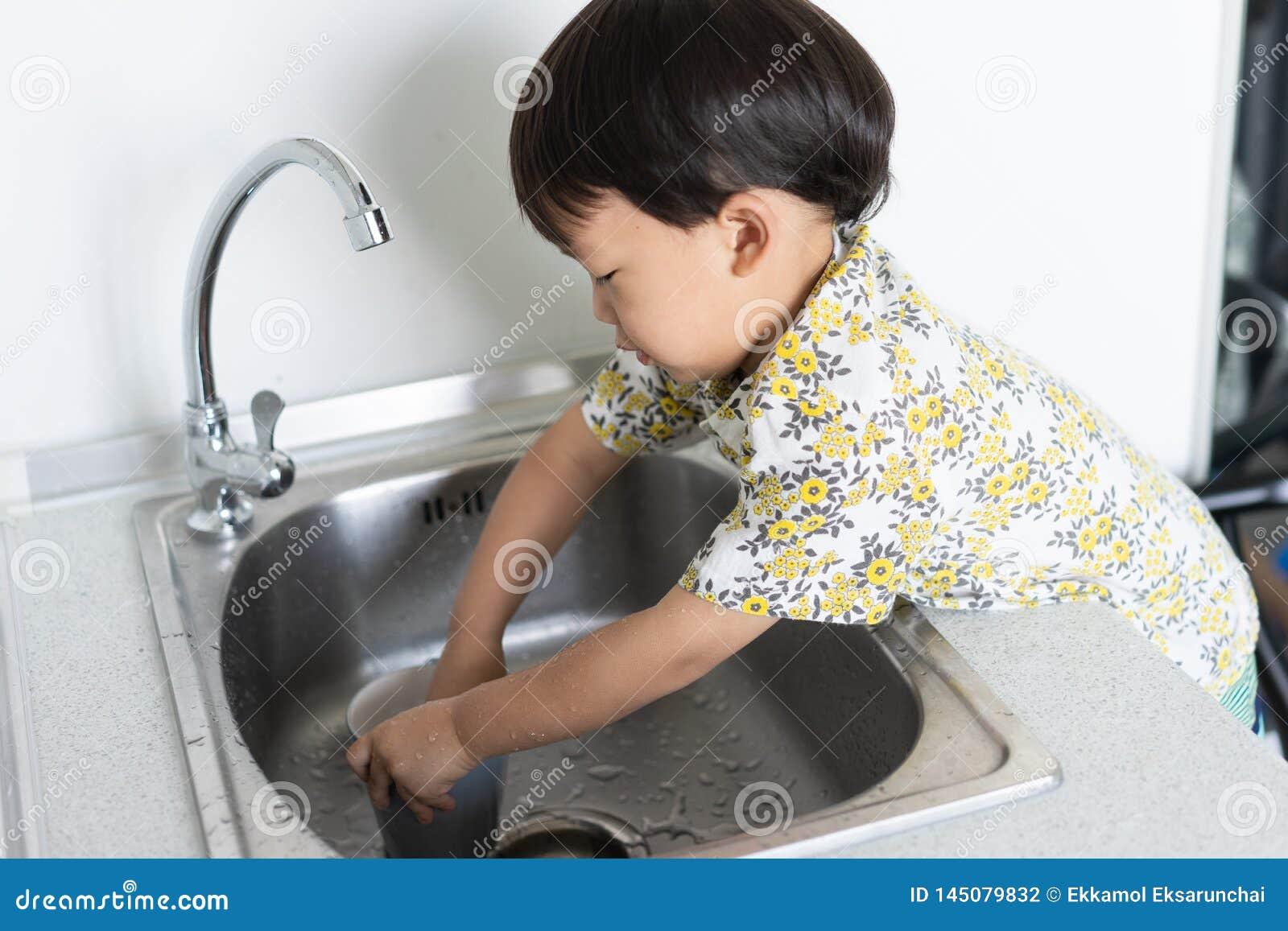 Το αγόρι βοηθά τη μητέρα για να κάνει τα οικιακά με το πλύσιμο ενός γυα
