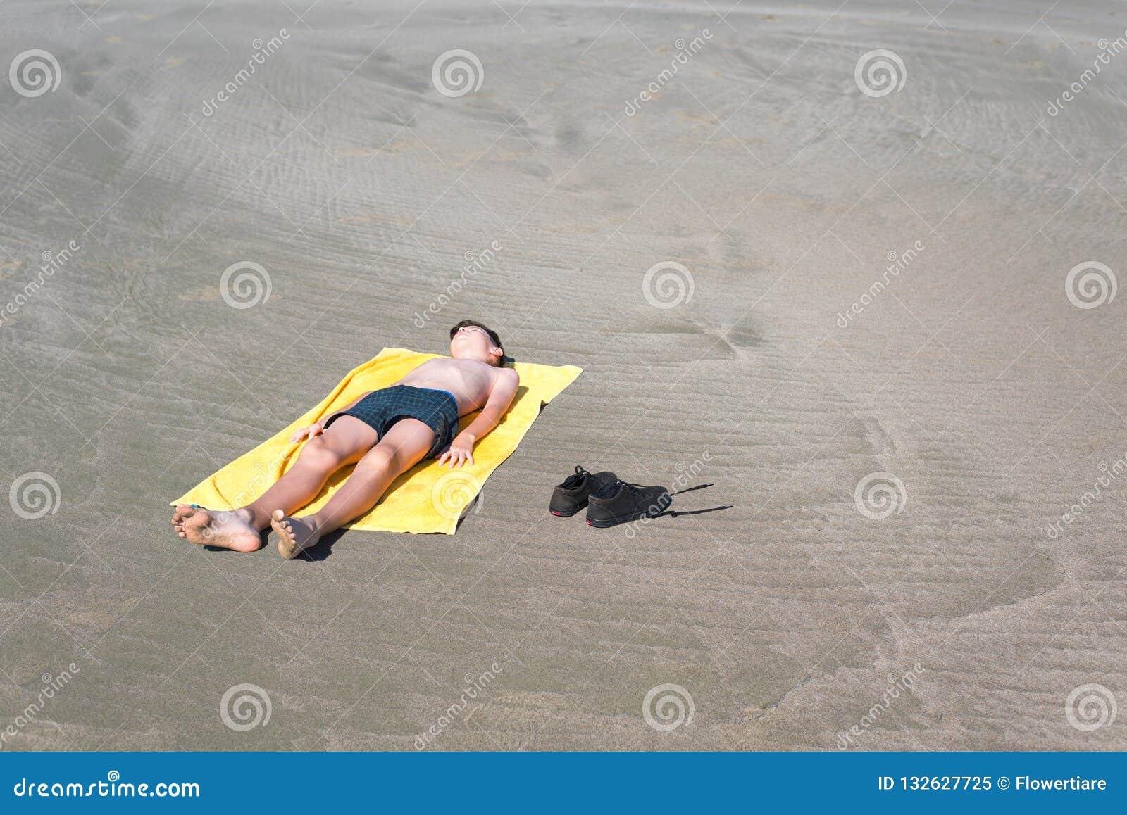 Το αγόρι εφήβων βρίσκεται στην κίτρινη πετσέτα και κάνει ηλιοθεραπεία στην παραλία Ταξίδι σε ένα αεροπλάνο με τα παιδιά