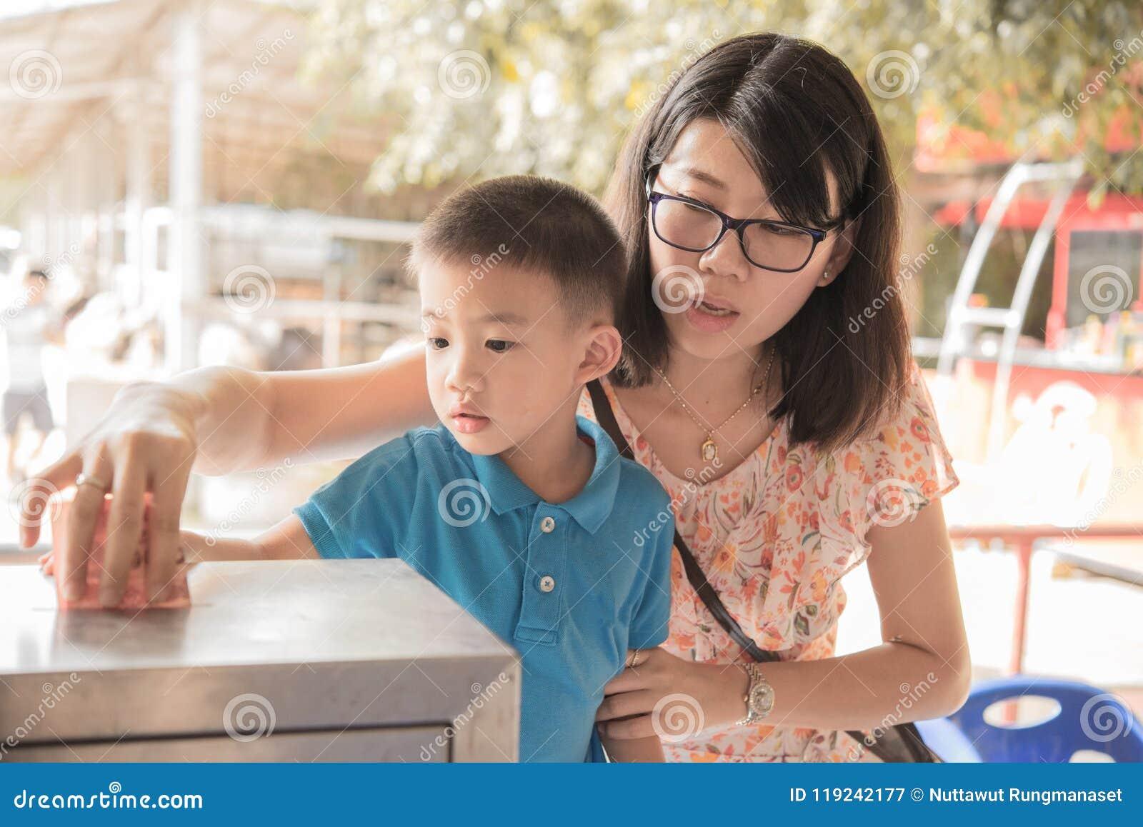 Το αγόρι και η μητέρα του όλο το toghter δίνουν τα κοντά τεθειμένα χρήματα στο κιβώτιο δωρεάς