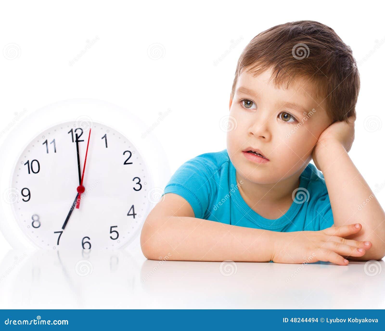Το αγόρι κρατά το μεγάλο ρολόι