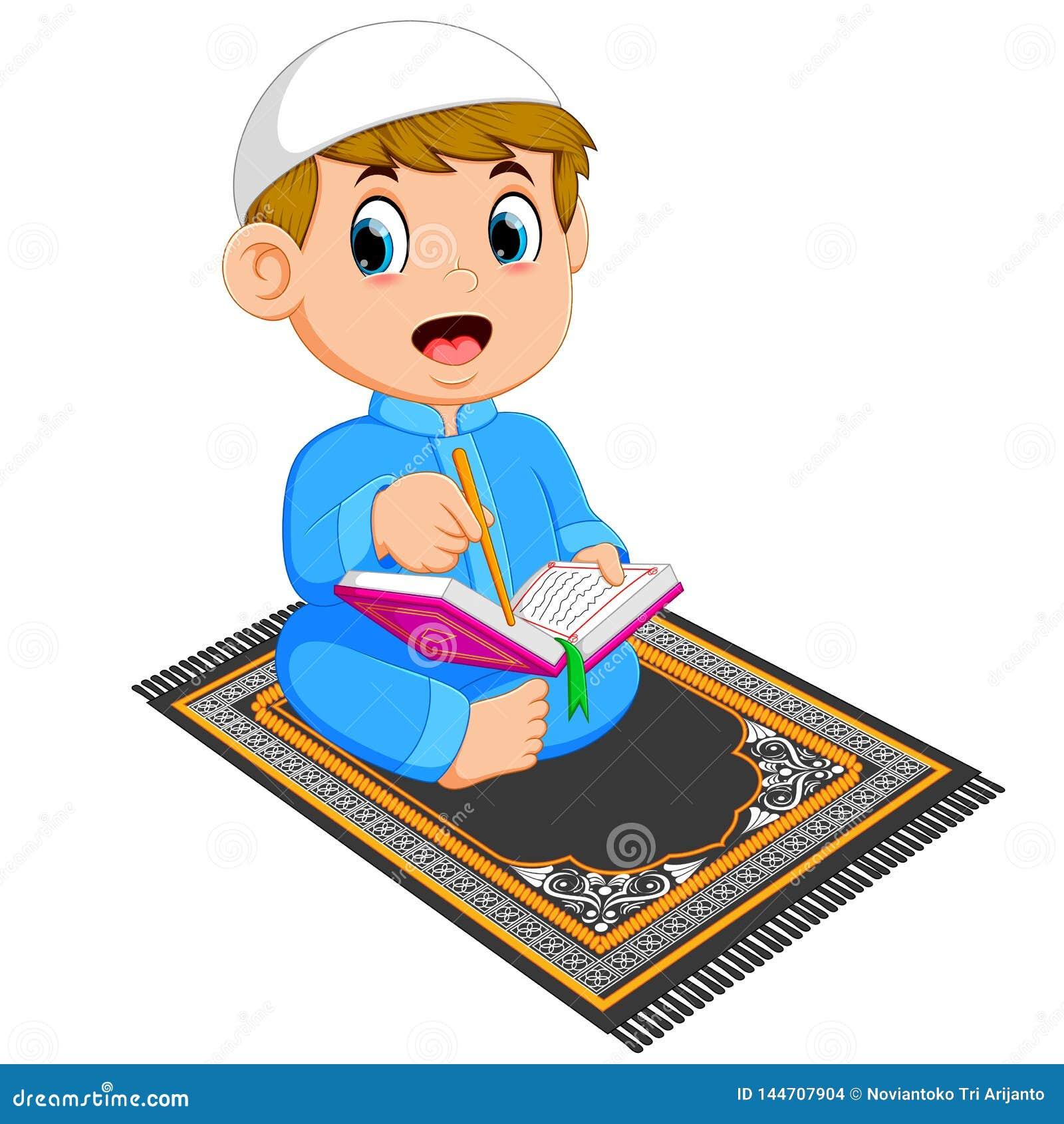 Το αγόρι με το μπλε καφτάνι διαβάζει το quran Al στην κουβέρτα προσευχής