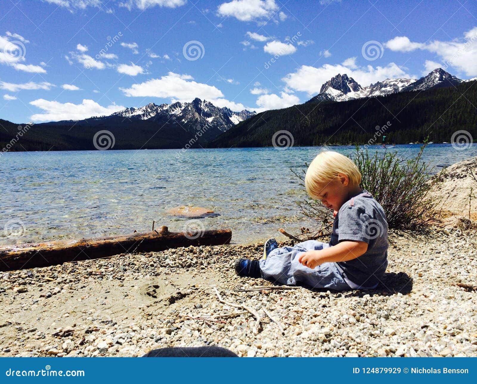 Το αγόρι μικρών παιδιών κάθεται στην άκρη της κόκκινης λίμνης ψαριών, που πηδά τους βράχους