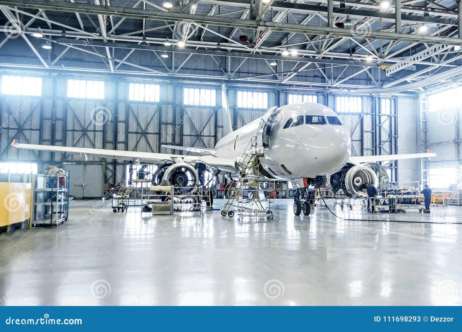 Το αεροπλάνο επιβατών στη συντήρηση της μηχανής και η άτρακτος ελέγχουν την επισκευή στο υπόστεγο αερολιμένων