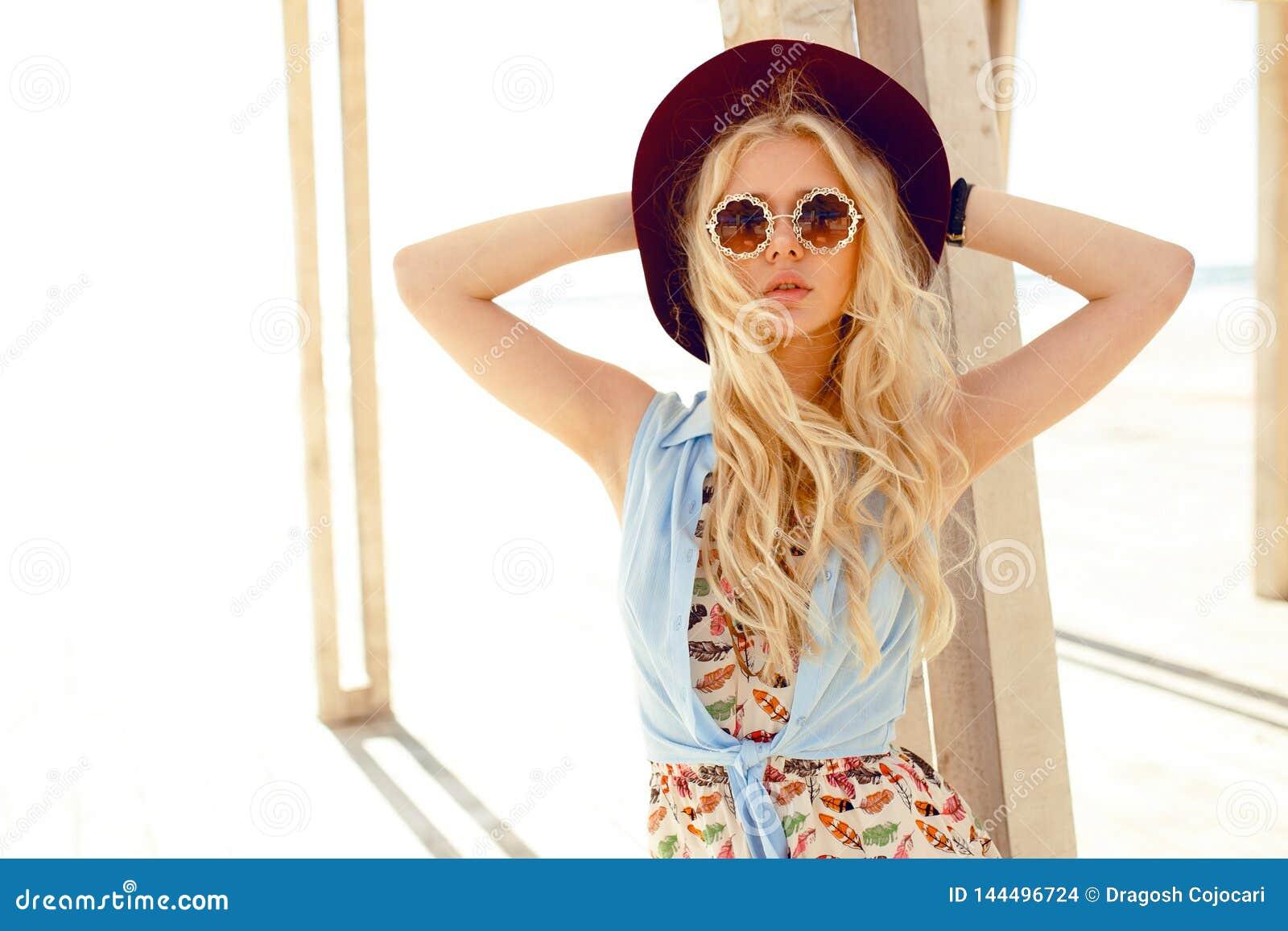 Το αισθησιακό ξανθό κορίτσι με τα στρογγυλά γυαλιά ηλίου, χαριτωμένο φόρεμα, τρίχα κυμάτων και burgundy καπέλο, απολαμβάνει το φω