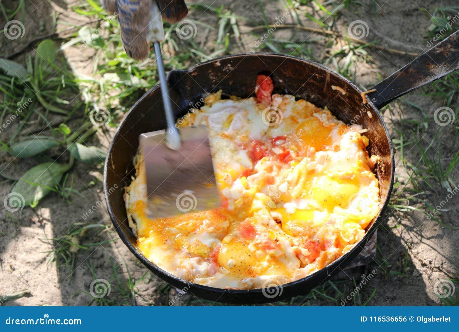 Το ανακατωμένο αυγό που τηγανίζεται στους άνθρακες στο τηγάνι ανοίγει πυρ επάνω, μαγειρεύει πέρα από ανοίγει πυρ