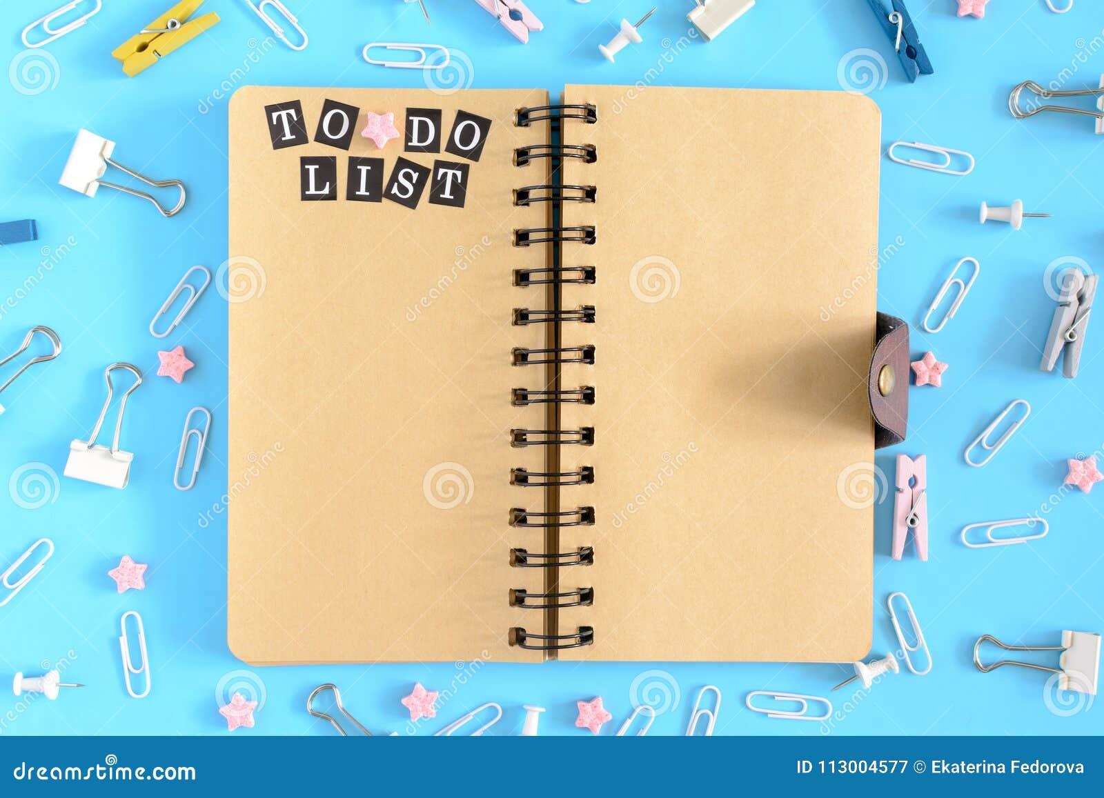 Το ανοικτό σημειωματάριο στο κέντρο βρωμίζει των χαρτικών Επιγραφές για να κάνει τον κατάλογο σε μια καφετιά σελίδα Συνδετήρες, c