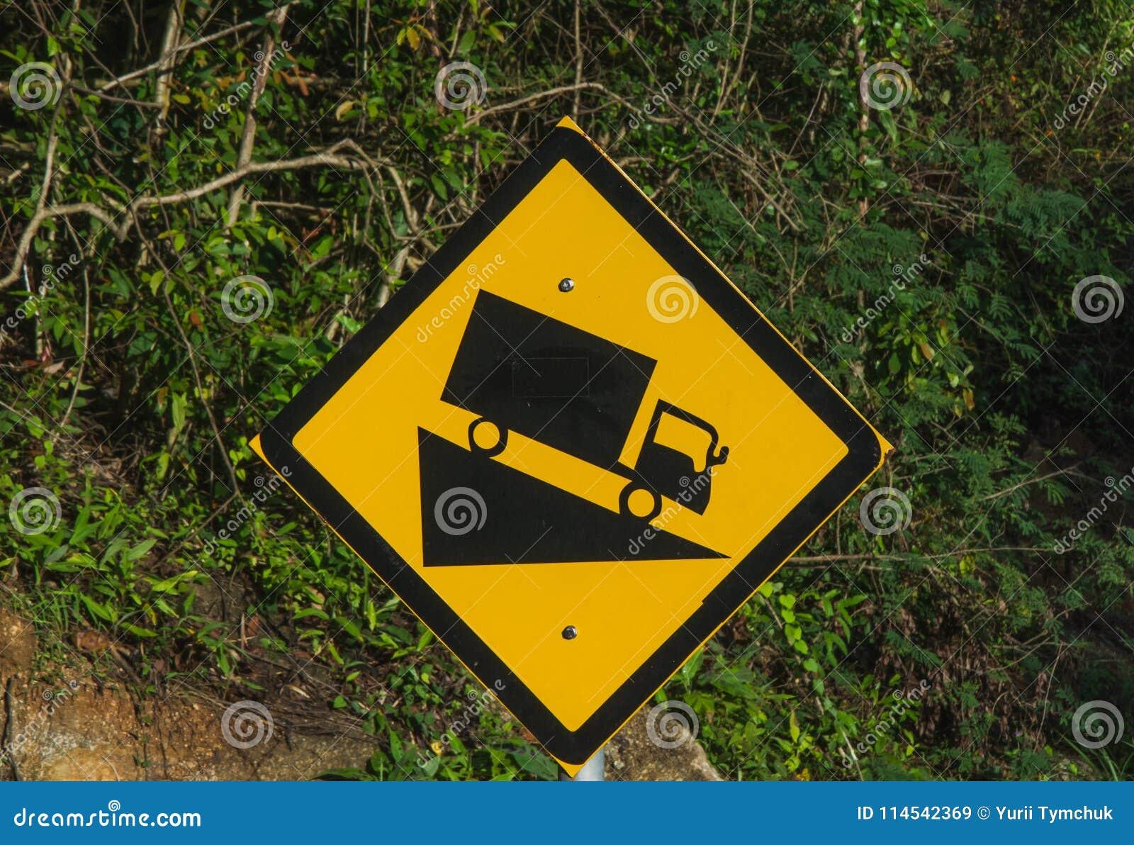 Το απότομο οδικό σημάδι witah ένα φορτηγό που οδηγεί κάτω από έναν απότομο υποβιβάζει μαύρος και κίτρινος στο οδικό σημάδι τροπικ