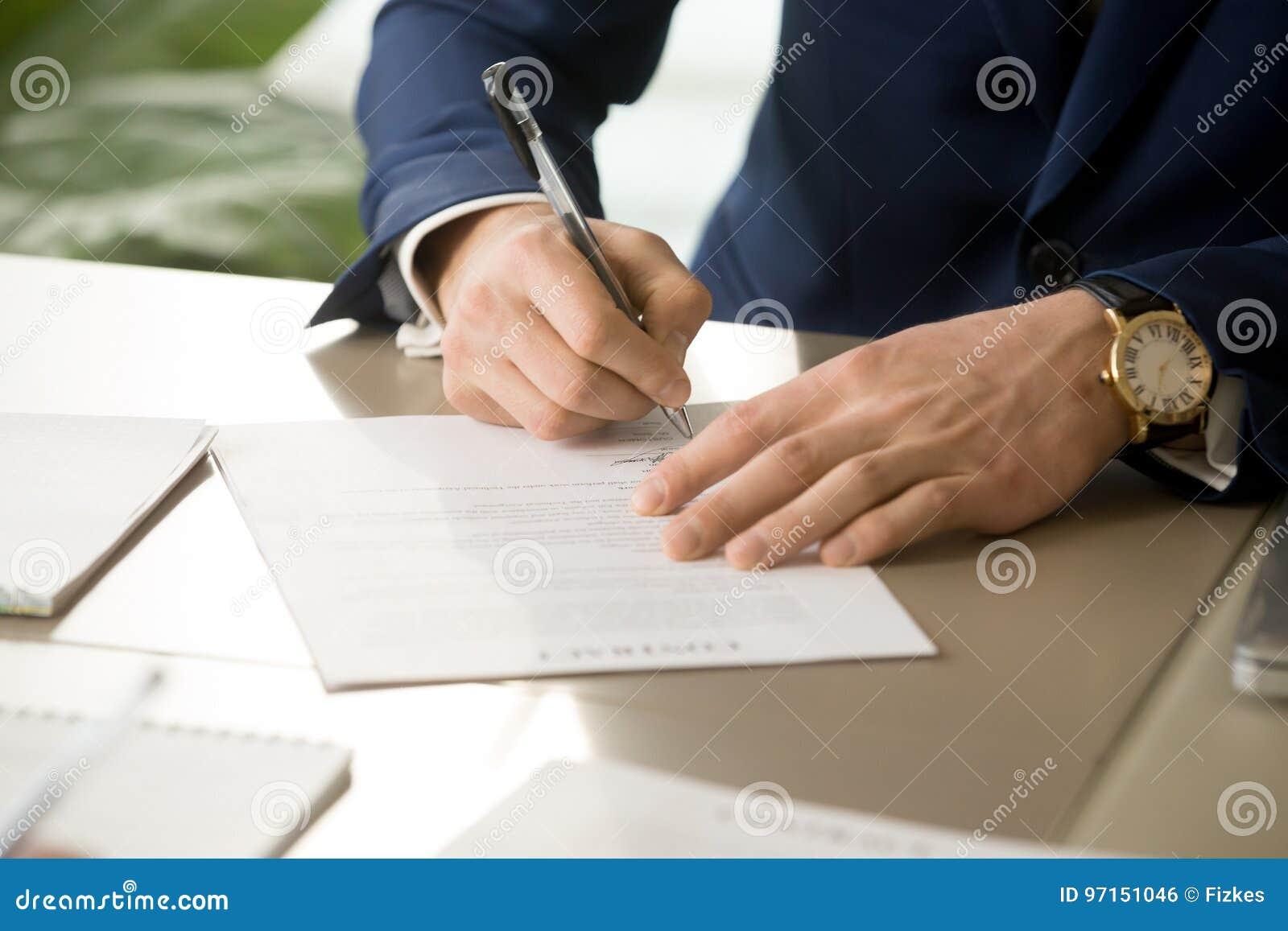 Το αρσενικό χέρι που βάζει την υπογραφή στη σύμβαση, που υπογράφει το έγγραφο, κλείνει
