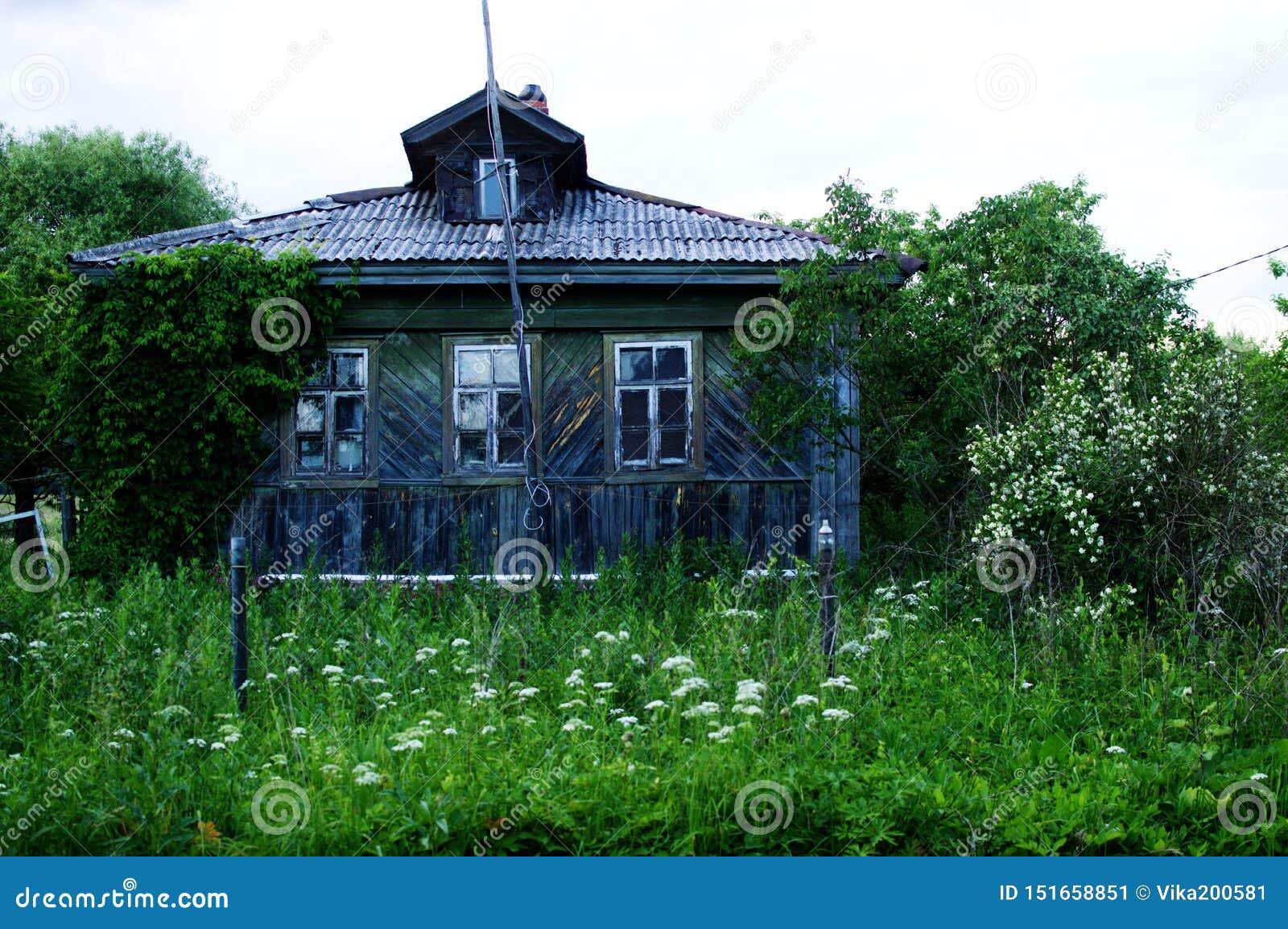Το αρχαίο εγκαταλειμμένο ξύλινο σπίτι με έναν κήπο