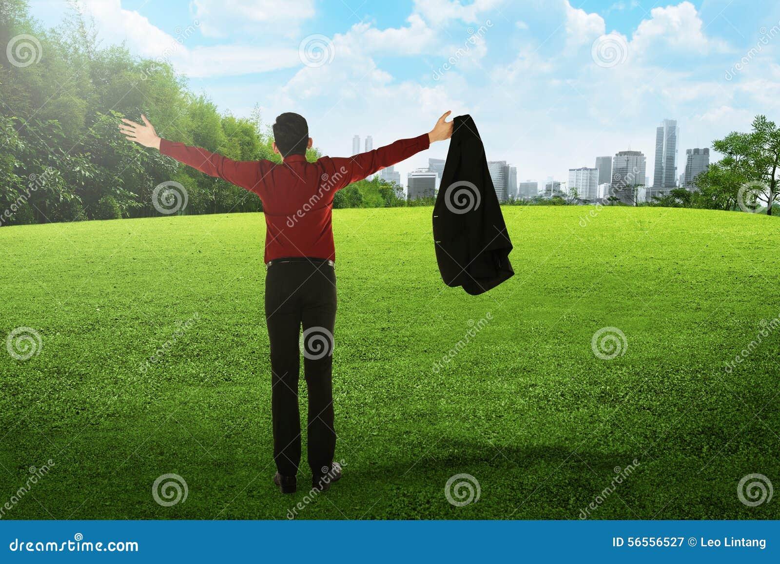 Download Το ασιατικό επιχειρησιακό άτομο ανοίγει το κοστούμι του στο πάρκο πόλεων Στοκ Εικόνα - εικόνα από ασιατικοί, πράσινος: 56556527