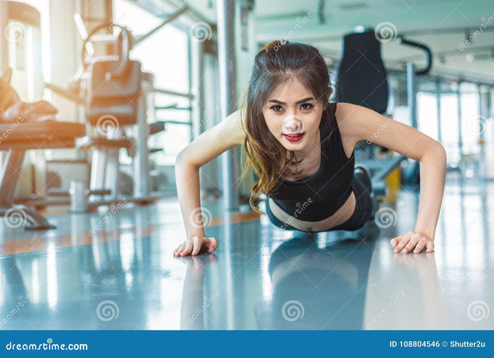 Το ασιατικό κορίτσι ικανότητας γυναικών κάνει την ώθηση UPS στη γυμναστική ικανότητας Healthca