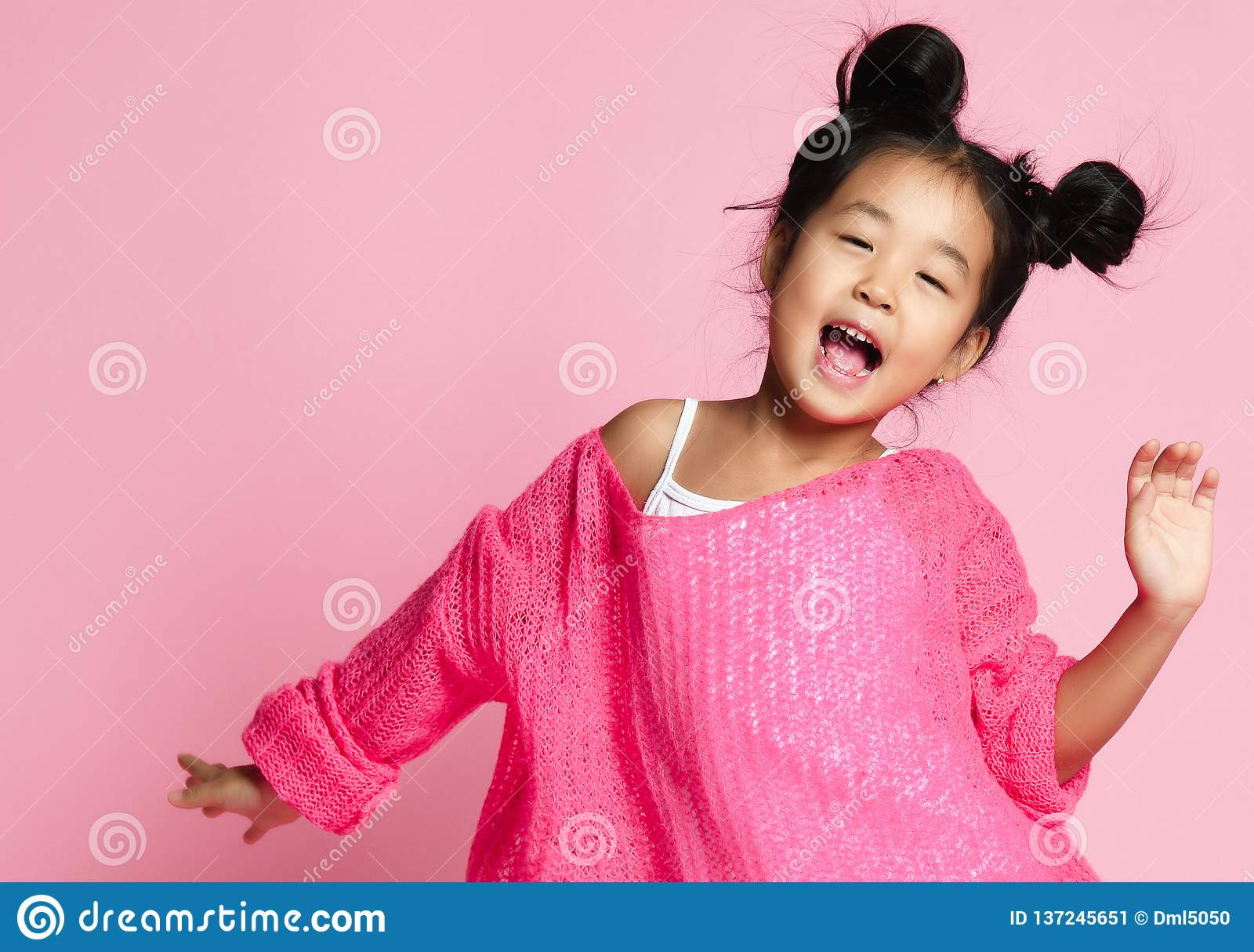 Το ασιατικό κορίτσι παιδιών στο ρόδινο πουλόβερ, τα άσπρα εσώρουχα και τα αστεία κουλούρια τραγουδά κλείστε επάνω