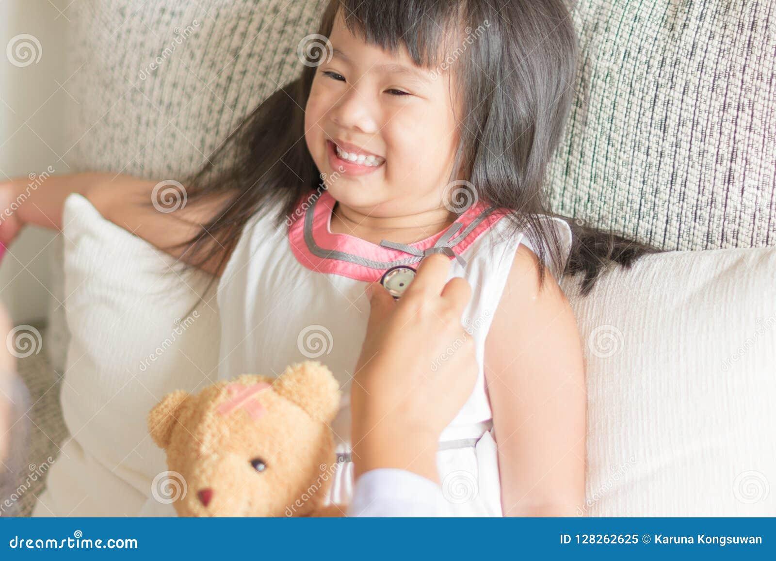 Το ασιατικό χαριτωμένο μικρό κορίτσι χαμογελά και παίζει το γιατρό με το stetho