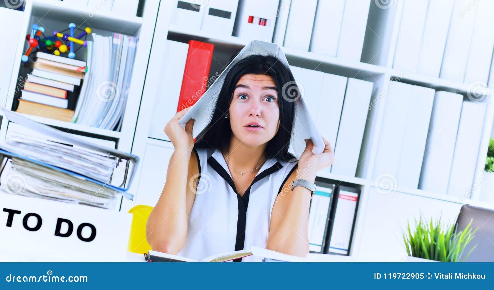 Το αστείο καταπονημένο κορίτσι με έναν φάκελλο στην επικεφαλής συνεδρίασή της στον εργασιακό χώρο σωρίασε με τους φακέλλους Αντίδ