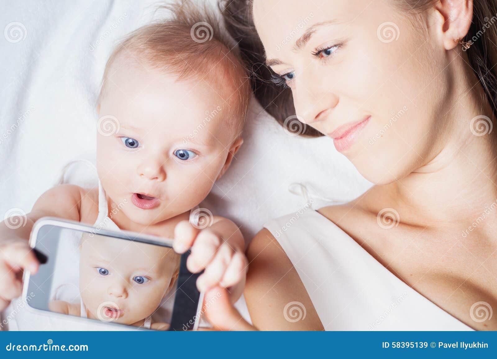 Το αστείο κοριτσάκι με το mom κάνει selfie στο κινητό τηλέφωνο