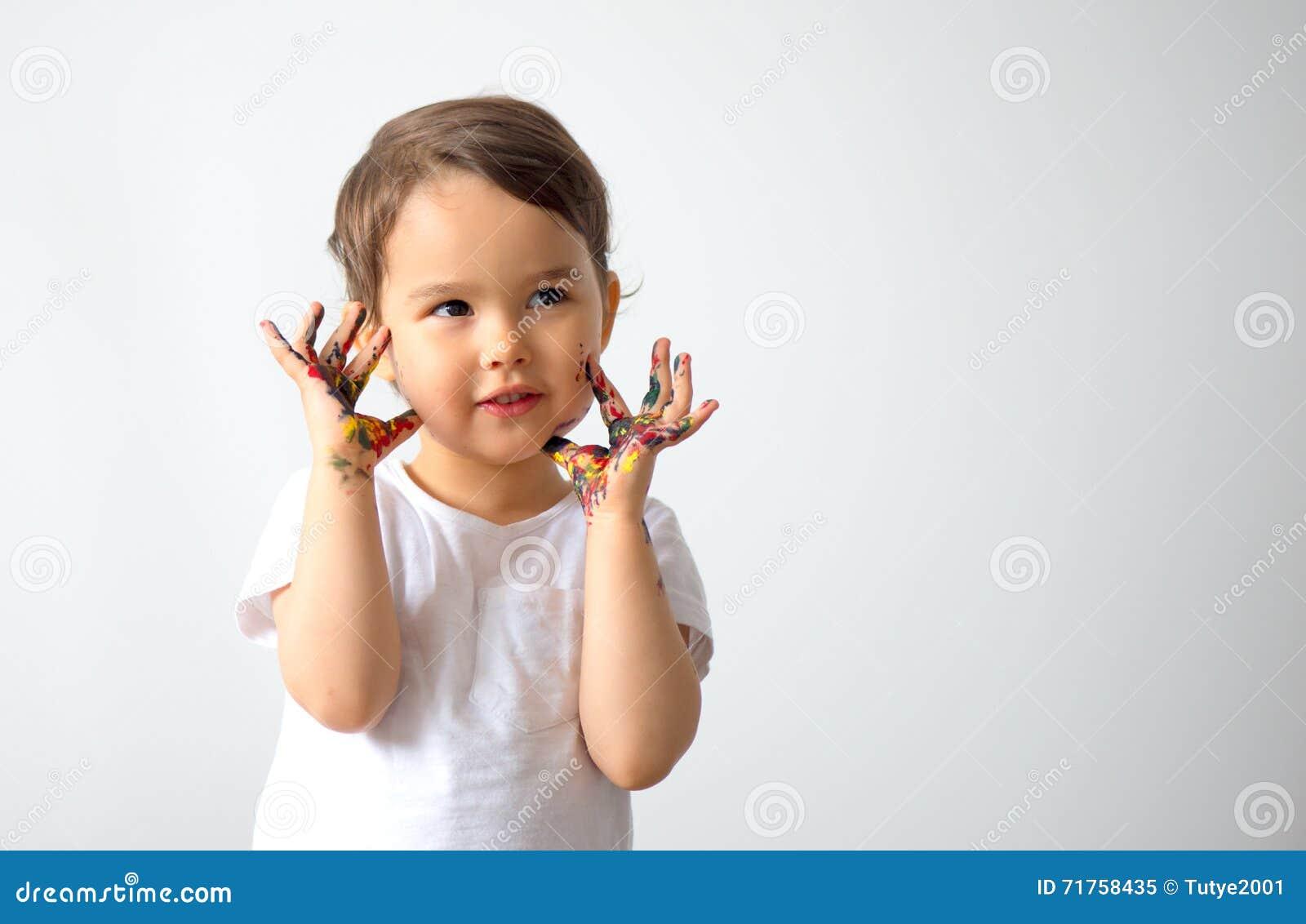 Το αστείο μικρό κορίτσι με τα χέρια χρωμάτισε στο ζωηρόχρωμο χρώμα απομονωμένος
