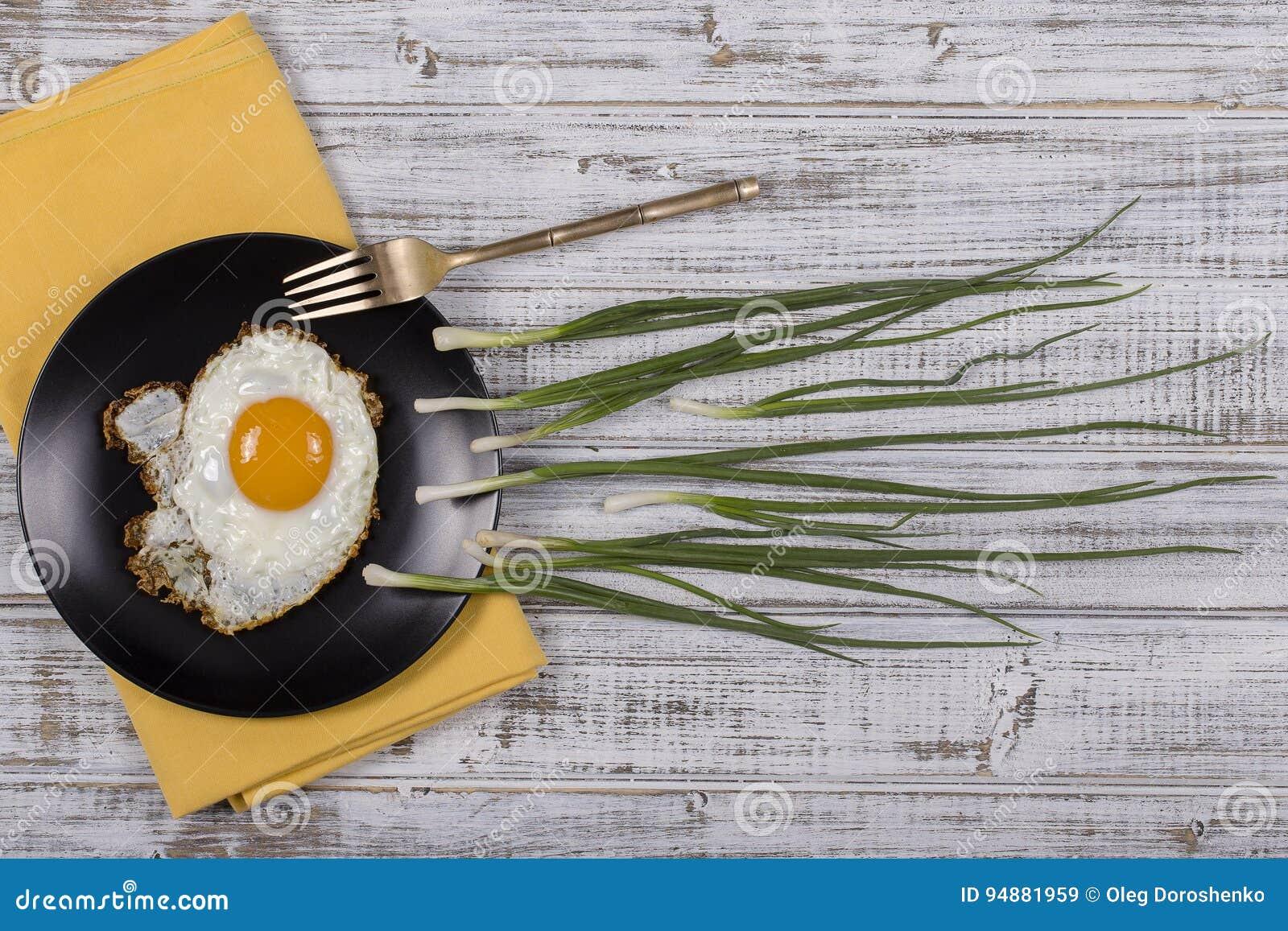 Το αυγό, τα φρέσκα κρεμμύδια και το μαύρο πιάτο μοιάζουν με τον ανταγωνισμό σπέρματος, Spermatozoons που επιπλέει στο ωάριο στο ά