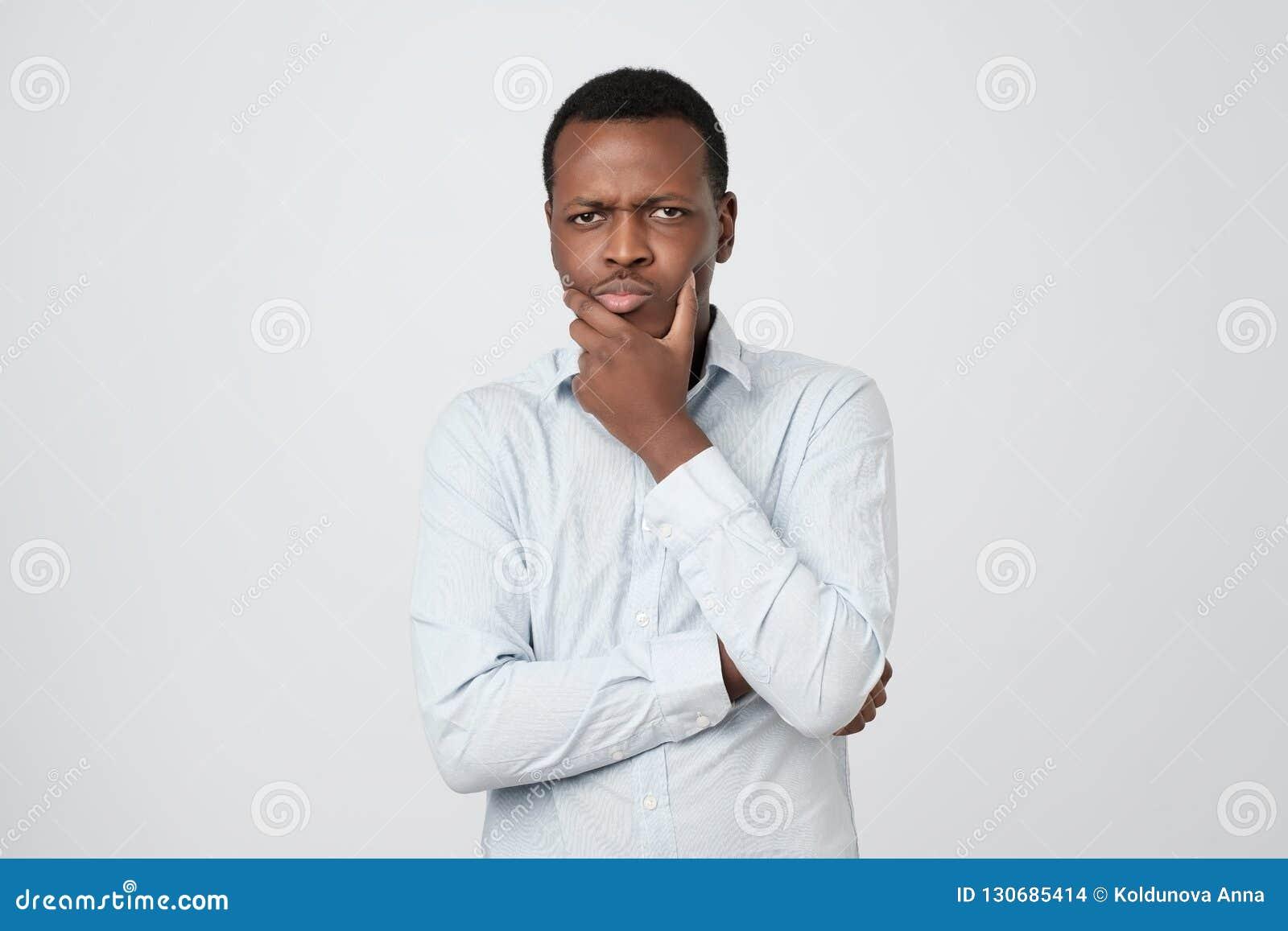 Το αφρικανικό νέο σκεπτόμενο άτομο ανατρέχει με το χέρι κοντά στο πρόσωπο που απομονώνεται στο άσπρο υπόβαθρο