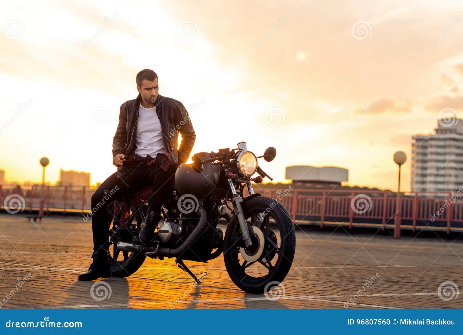 Το βάναυσο άτομο κάθεται στη μοτοσικλέτα συνήθειας δρομέων καφέδων