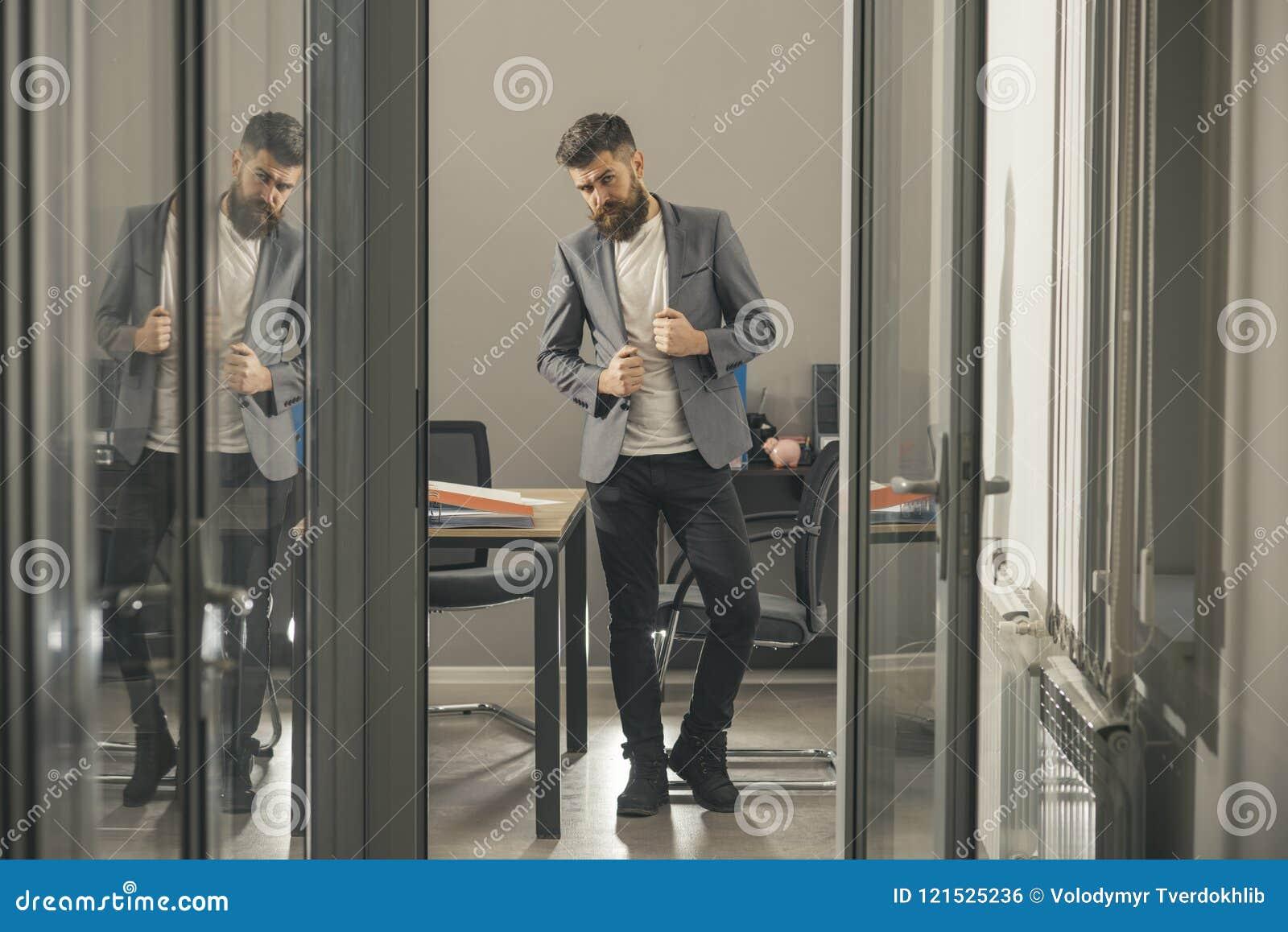 Το γενειοφόρο άτομο φαίνεται έξω πόρτα γραφείων Γενειοφόρο άτομο στο σύγχρονο γραφείο με τους τοίχους γυαλιού, επιχειρησιακός τρό