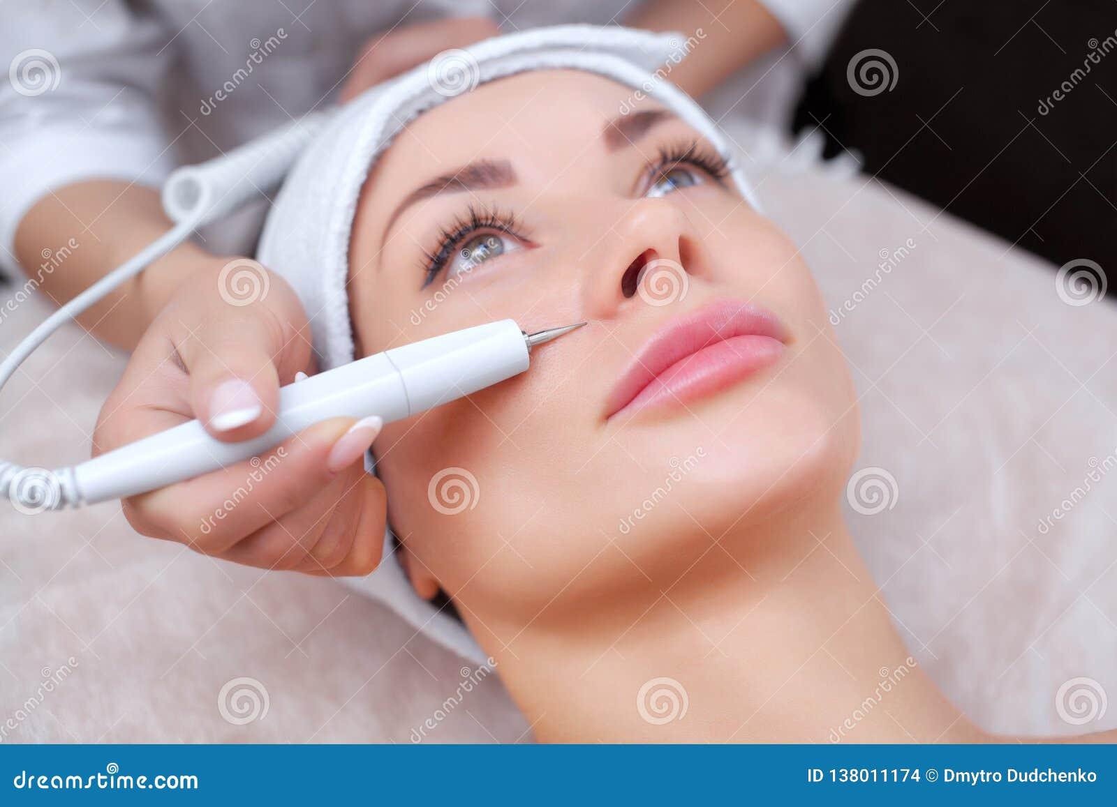 Το γιατρός-cosmetologist κάνει την επεξεργασία διαδικασίας Couperose του του προσώπου δέρματος μιας όμορφης, νέας γυναίκας
