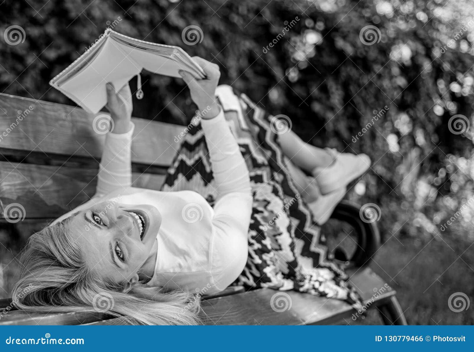 Το γυναικείο ευτυχές πρόσωπο απολαμβάνει Χρόνος για τη μόνη βελτίωση Το κορίτσι βάζει τη χαλάρωση πάρκων πάγκων με το βιβλίο, πρά
