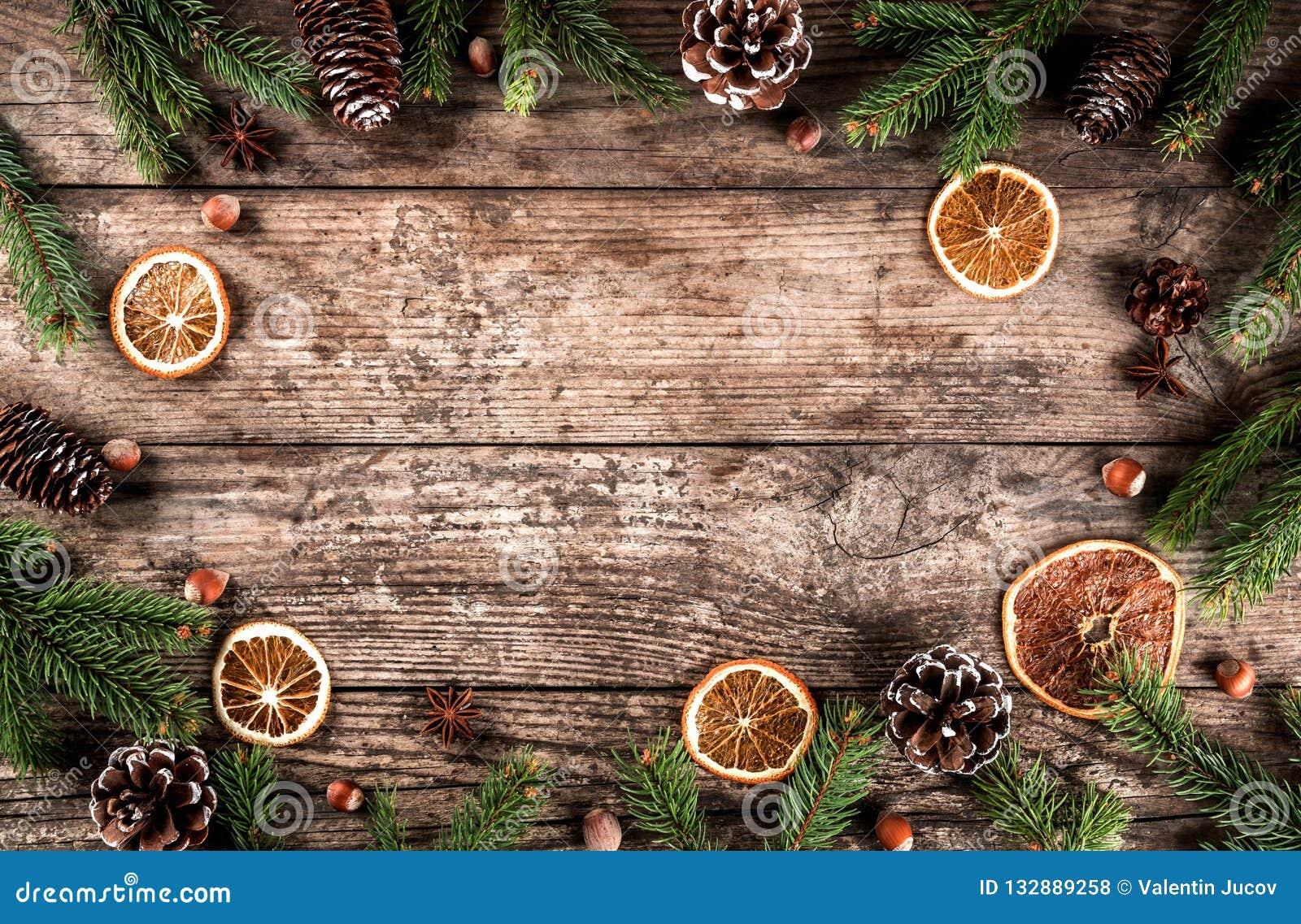 Το δημιουργικό πλαίσιο σχεδιαγράμματος φιαγμένο από έλατο Χριστουγέννων διακλαδίζεται, ερυθρελάτες, φέτες του πορτοκαλιού, κώνοι