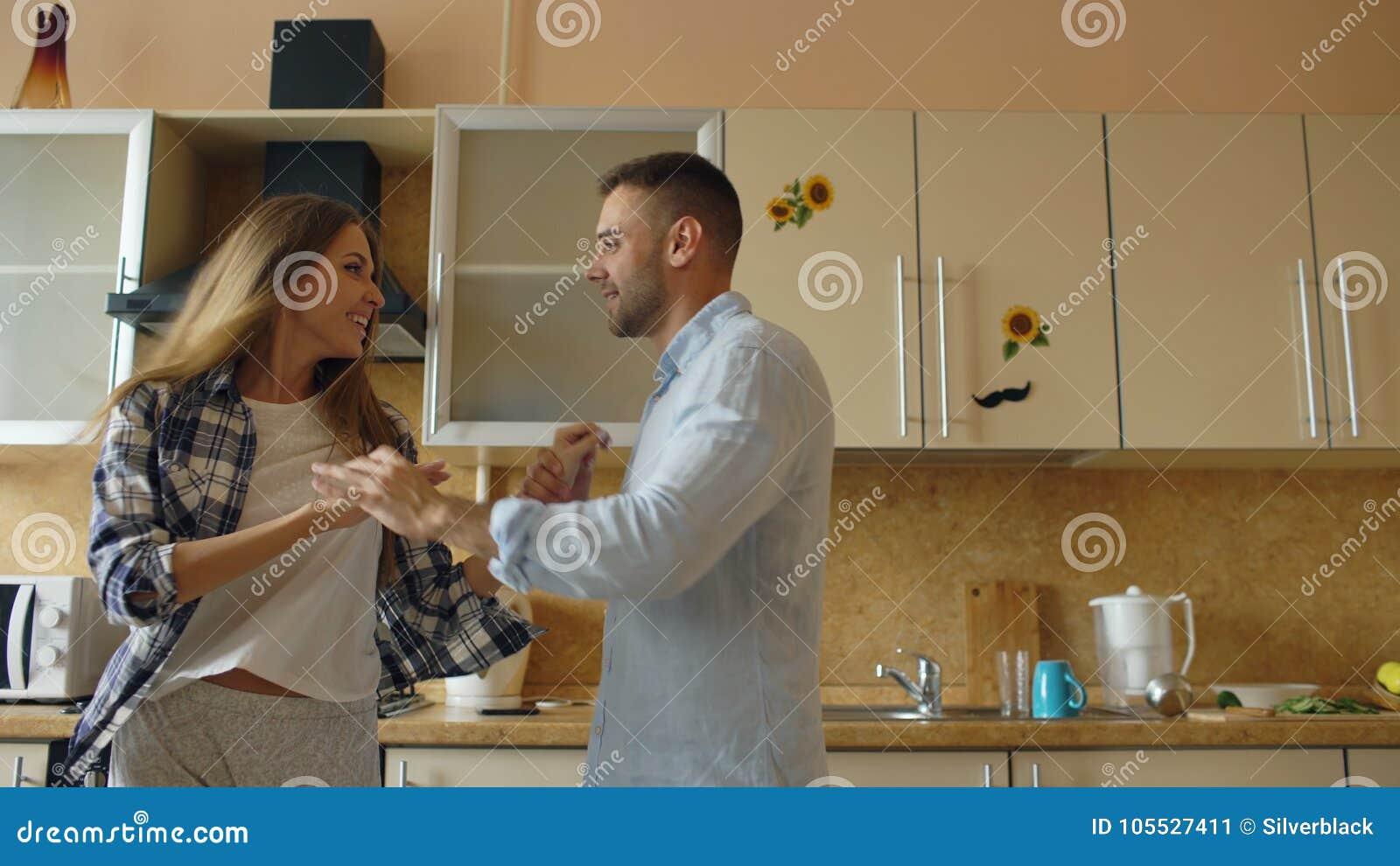Το ελκυστικό νέο αστείο ζεύγος έχει τη διασκέδαση χορεύοντας μαγειρεύοντας στην κουζίνα στο σπίτι