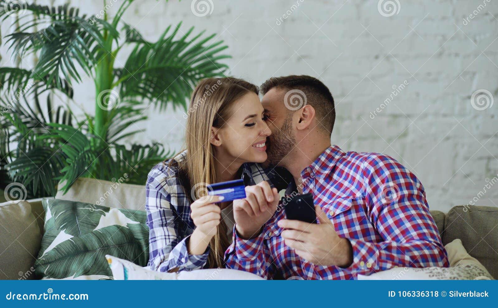 Το ελκυστικό νέο ζεύγος με το smartphone και η πιστωτική κάρτα που ψωνίζει στο διαδίκτυο κάθονται στον καναπέ στο καθιστικό στο σ