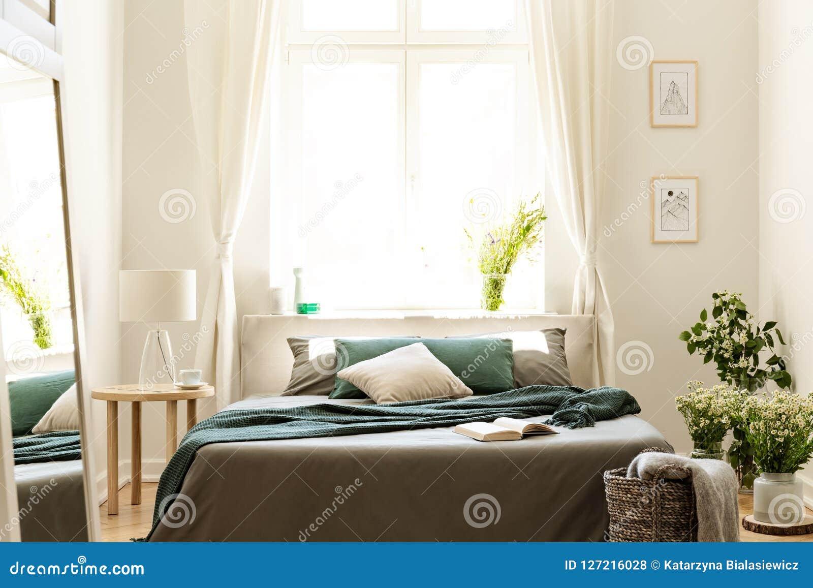 Το εσωτερικό κρεβατοκάμαρων στα χρώματα φύσης με το μεγάλο κρεβάτι, το γκρίζα και πράσινα λινό και τα μαξιλάρια, φρέσκο λιβάδι αν