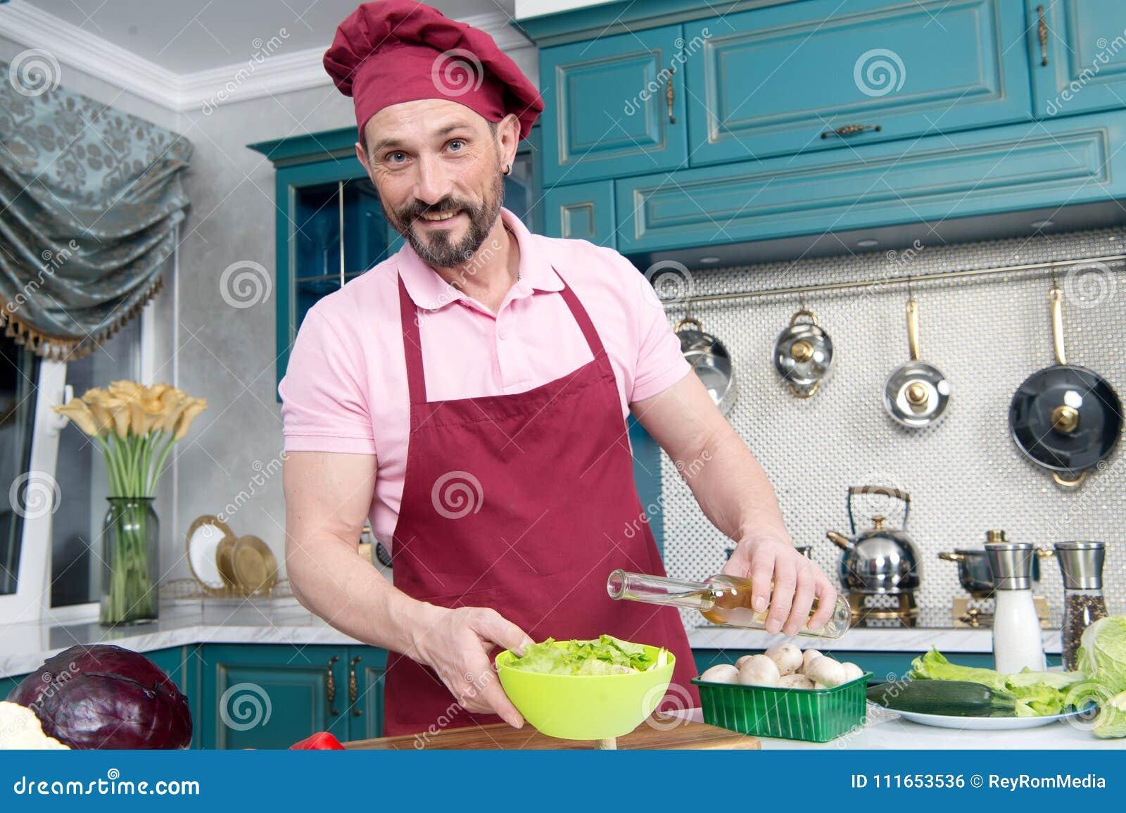 Το ευτυχές άτομο προσθέτει το πετρέλαιο στη φρέσκια σαλάτα Γενειοφόρος χαμογελασμένος αρχιμάγειρας που προσθέτει το ελαιόλαδο στη
