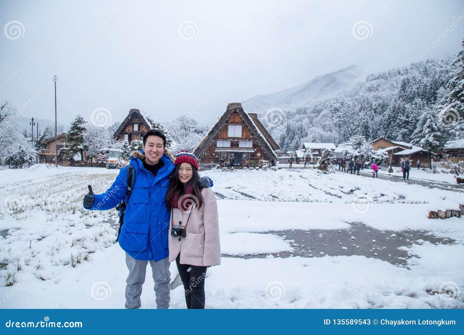 Το ευτυχές ασιατικό ζεύγος με να χιονίσει shirakawa-πηγαίνει μέσα