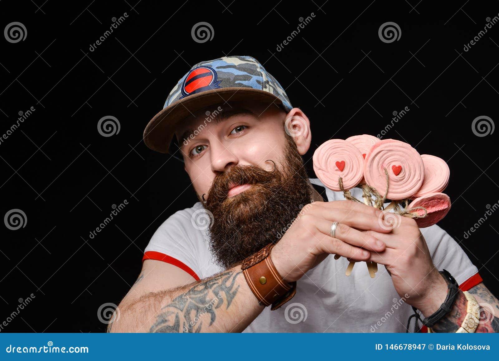 Το ευτυχές γενειοφόρο βάναυσο άτομο σε μια μοντέρνη ΚΑΠ κρατά ένα πακέτο των καραμελών lollipops