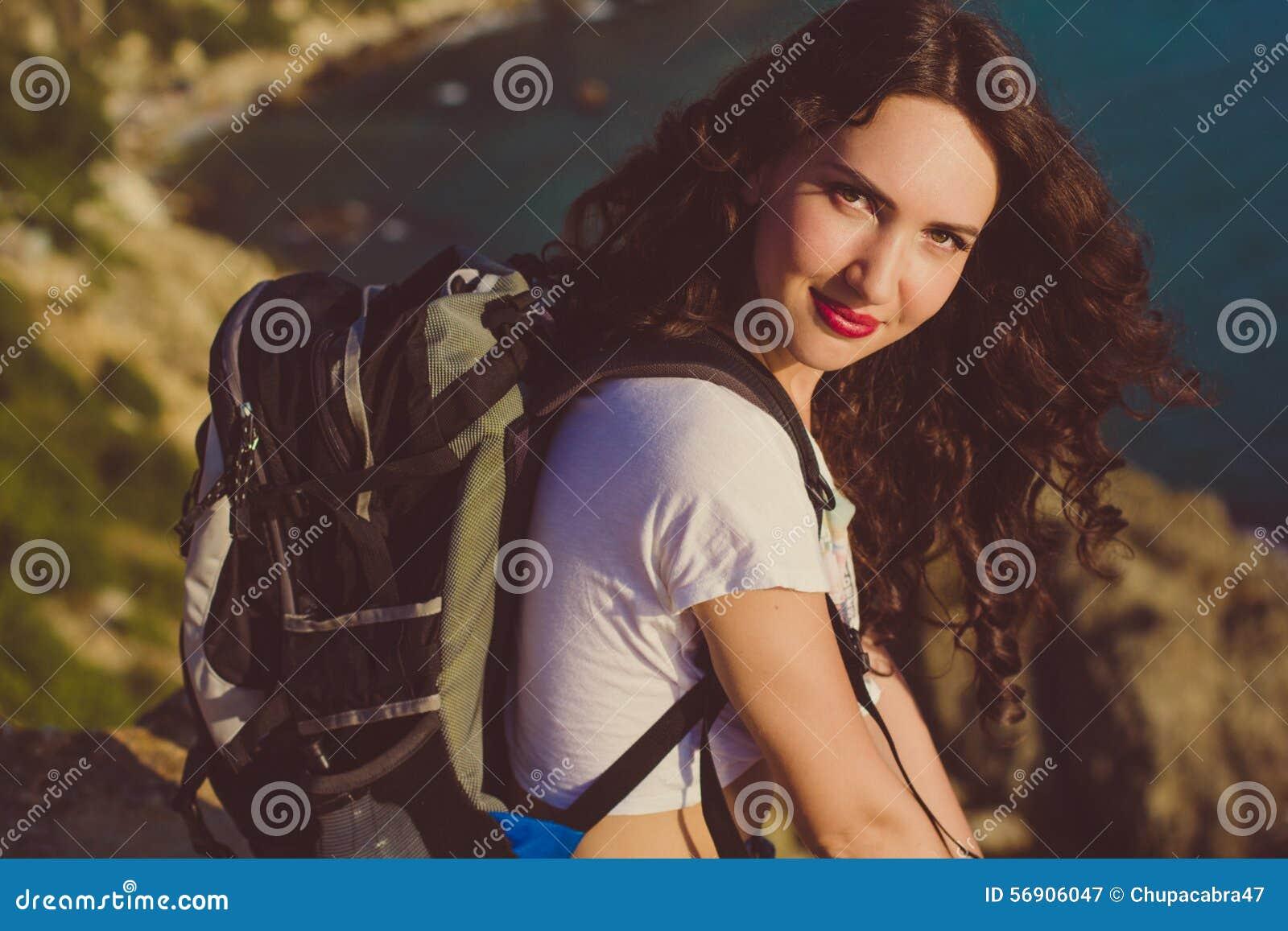 Το ευτυχές κορίτσι με το σακίδιο πλάτης κάθεται στην αιχμή βράχου